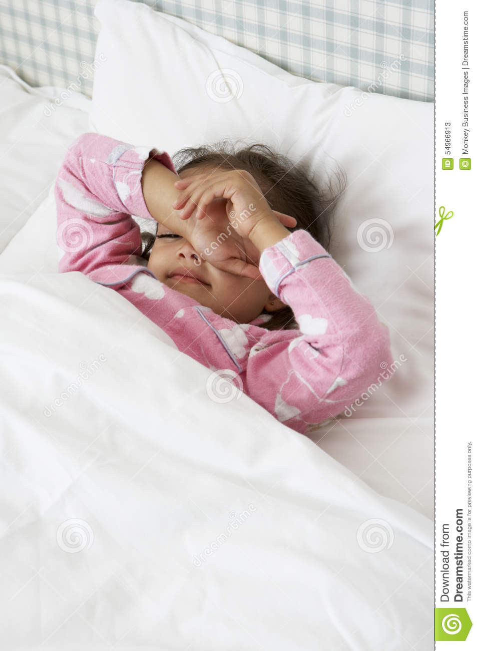 Tired Young Girl Wearing Pajamas In Bed Stock Photo