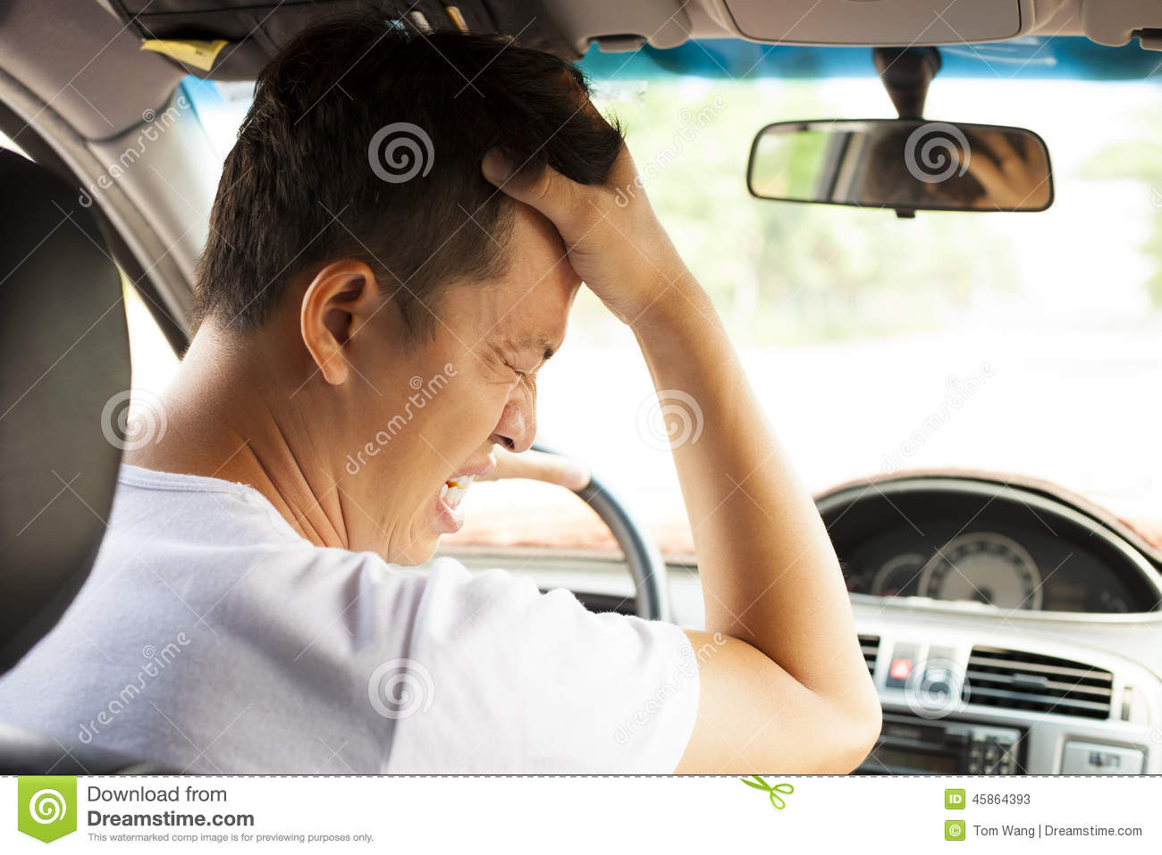 Tired young man have a headache while driving car.
