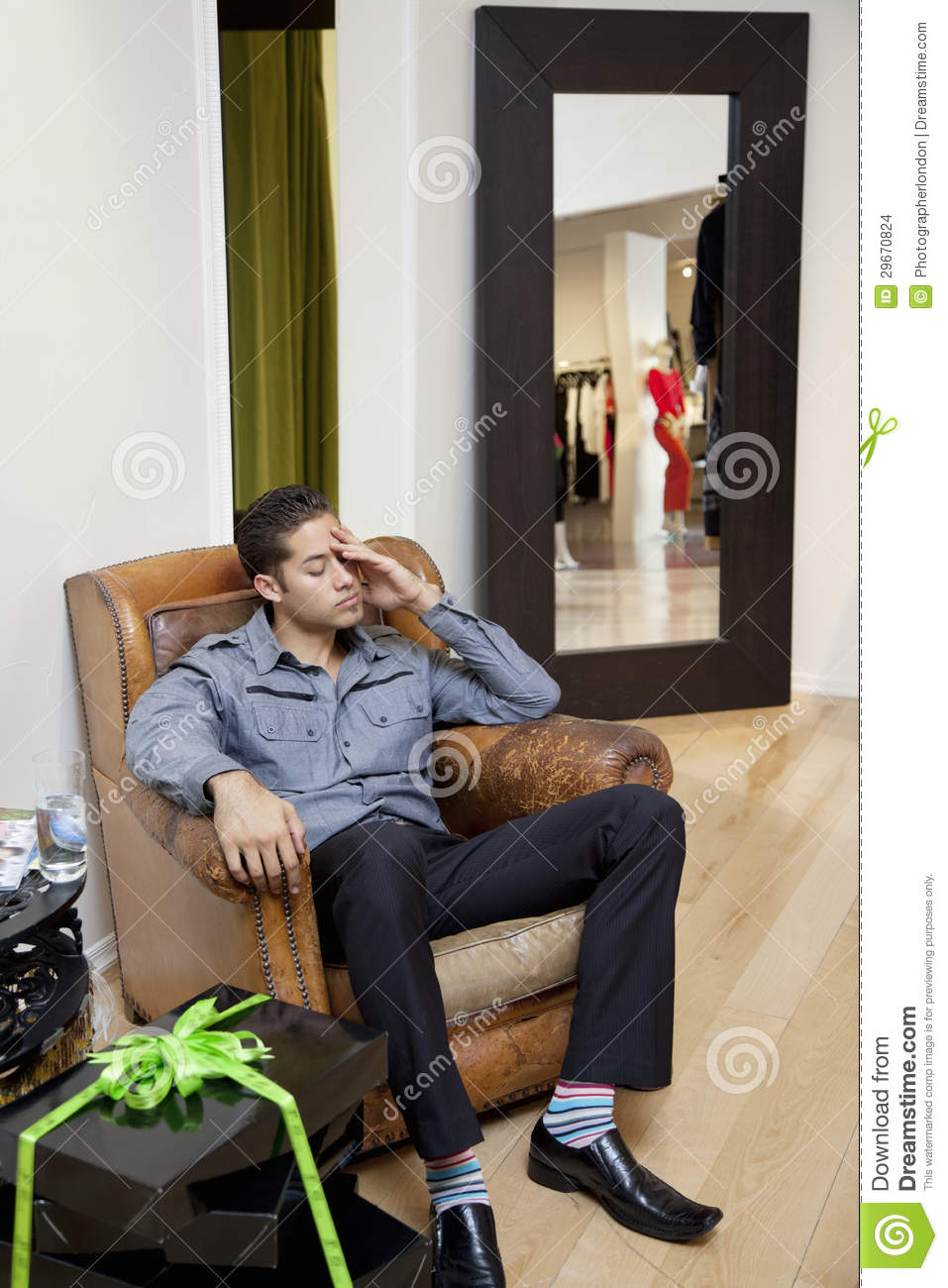 Tired young man sitting on armchair in fashion store stock for Sitting in armchair