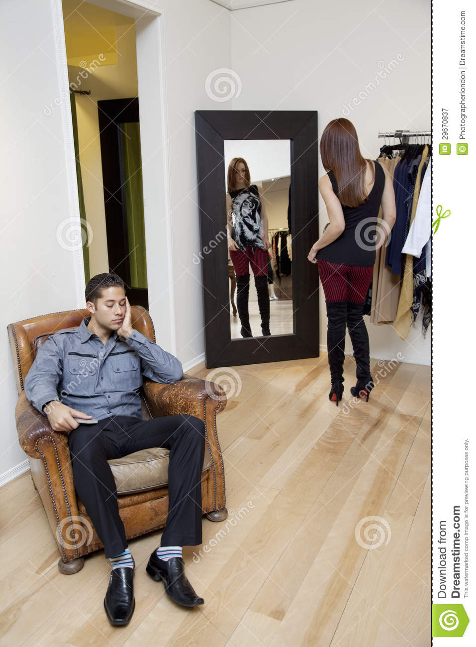 Tired young man sitting on armchair while woman looking at for Sitting in armchair