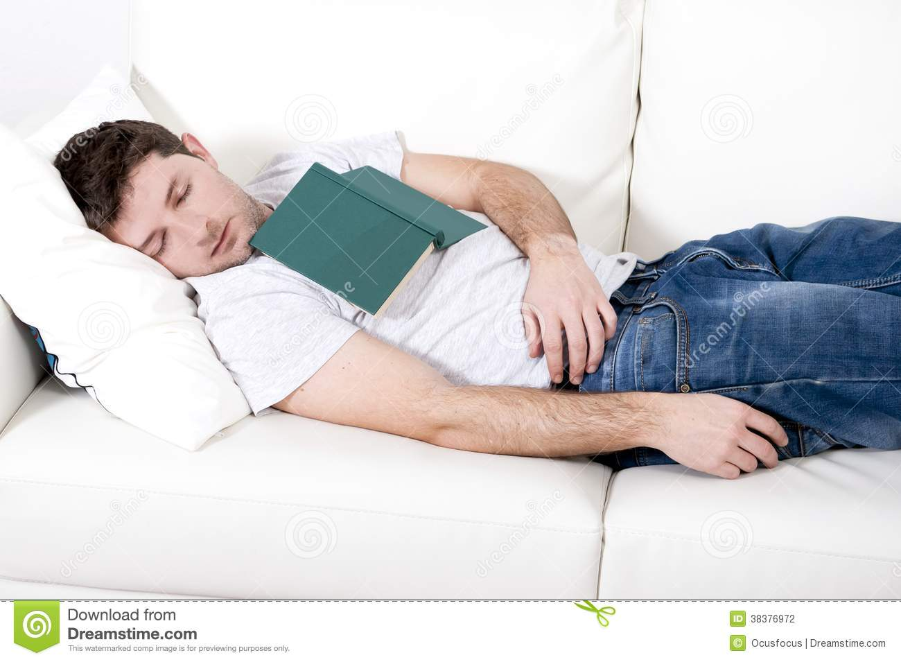 Tired Young Man Sleeping On Couch With Book On Lap Stock