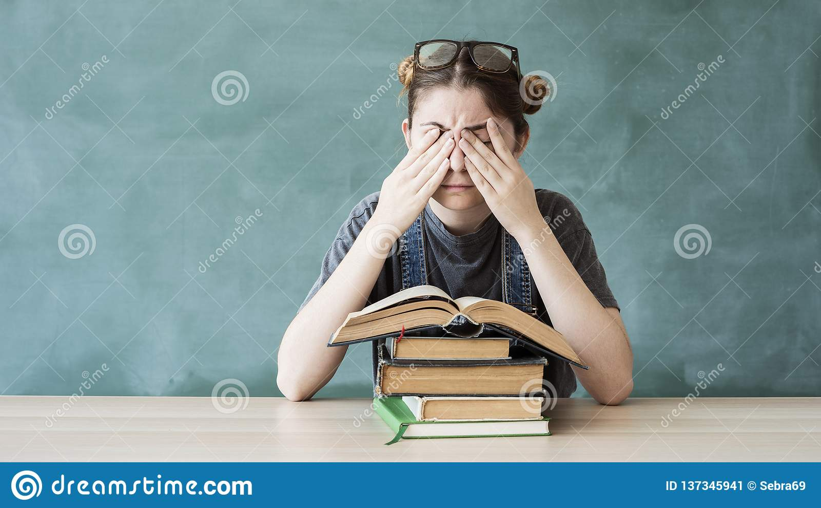 Tired young student girl with books