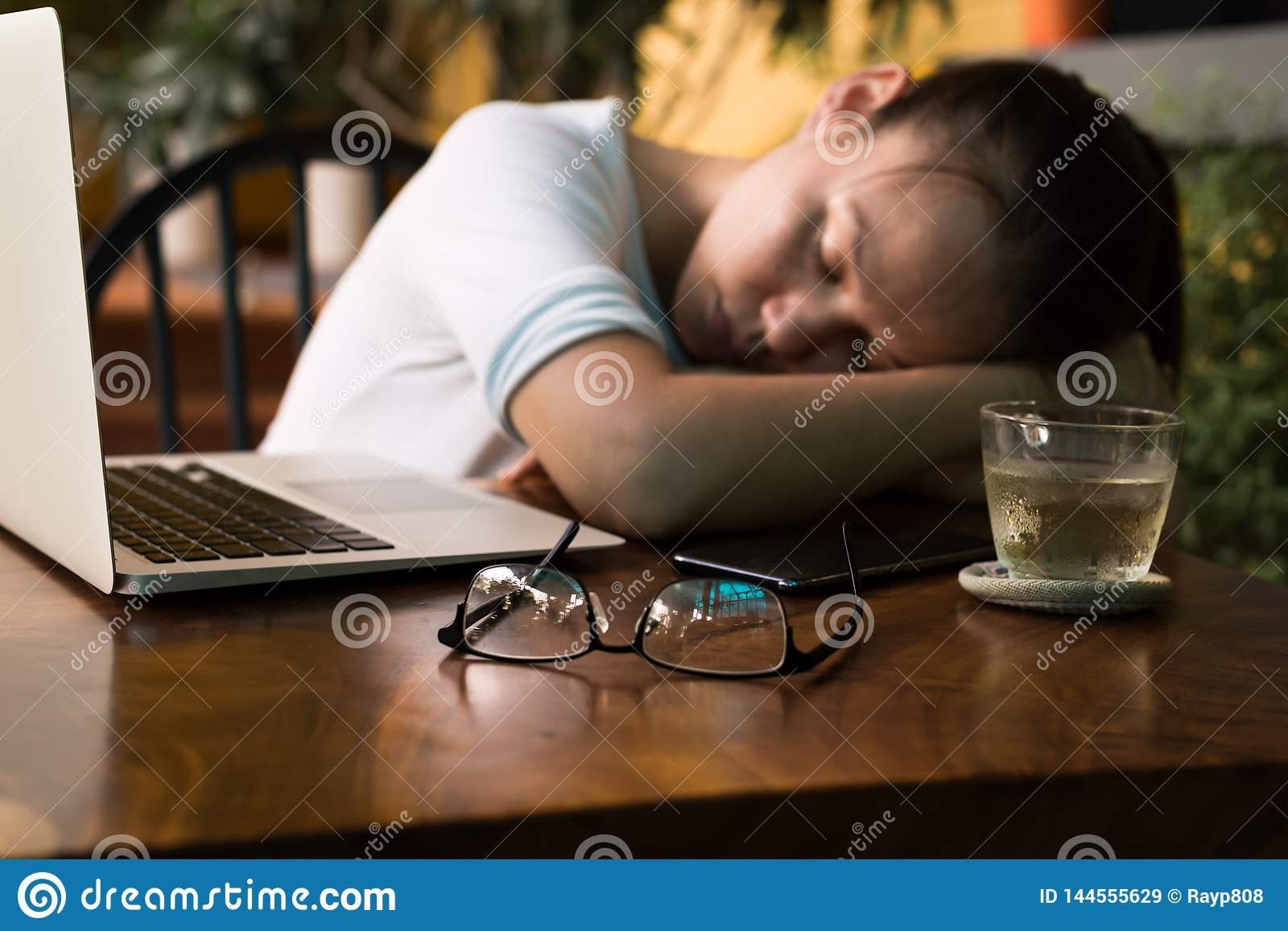 Tired young woman sleeping on her computer desk