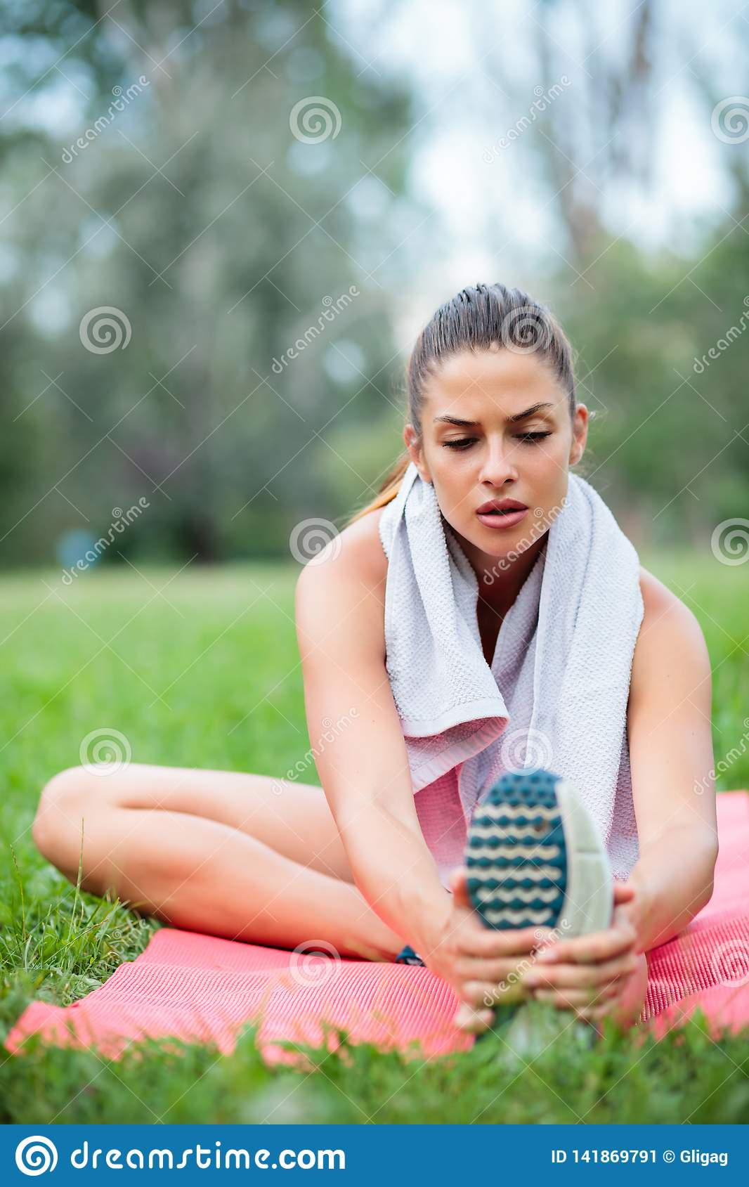 Tired young woman stretching after a workout in a park