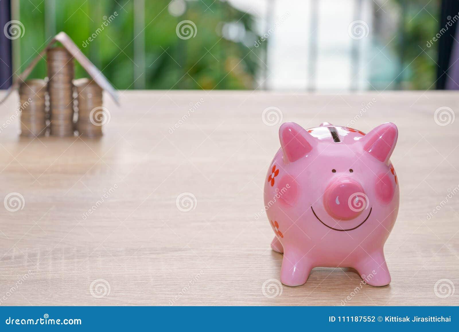 Tirelire rose sur le bureau en bois épargnez largent pour acheter