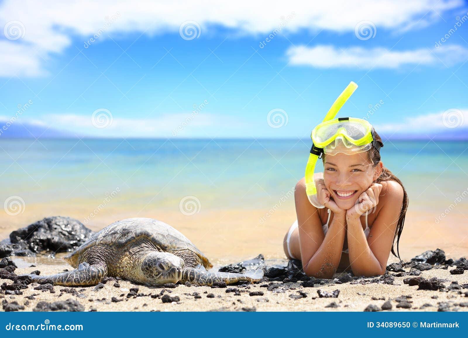 Tiri la donna in secco di viaggio sulle Hawai con la tartaruga di mare del mare