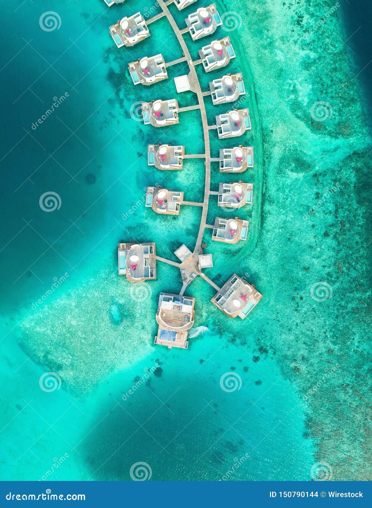 Tiro aéreo das casas construídas sobre o mar nas ilhas de Maldivas