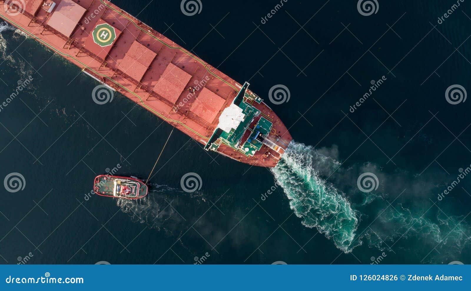 Tiro aéreo de um porto de aproximação do navio de carga com ajuda do navio do reboque