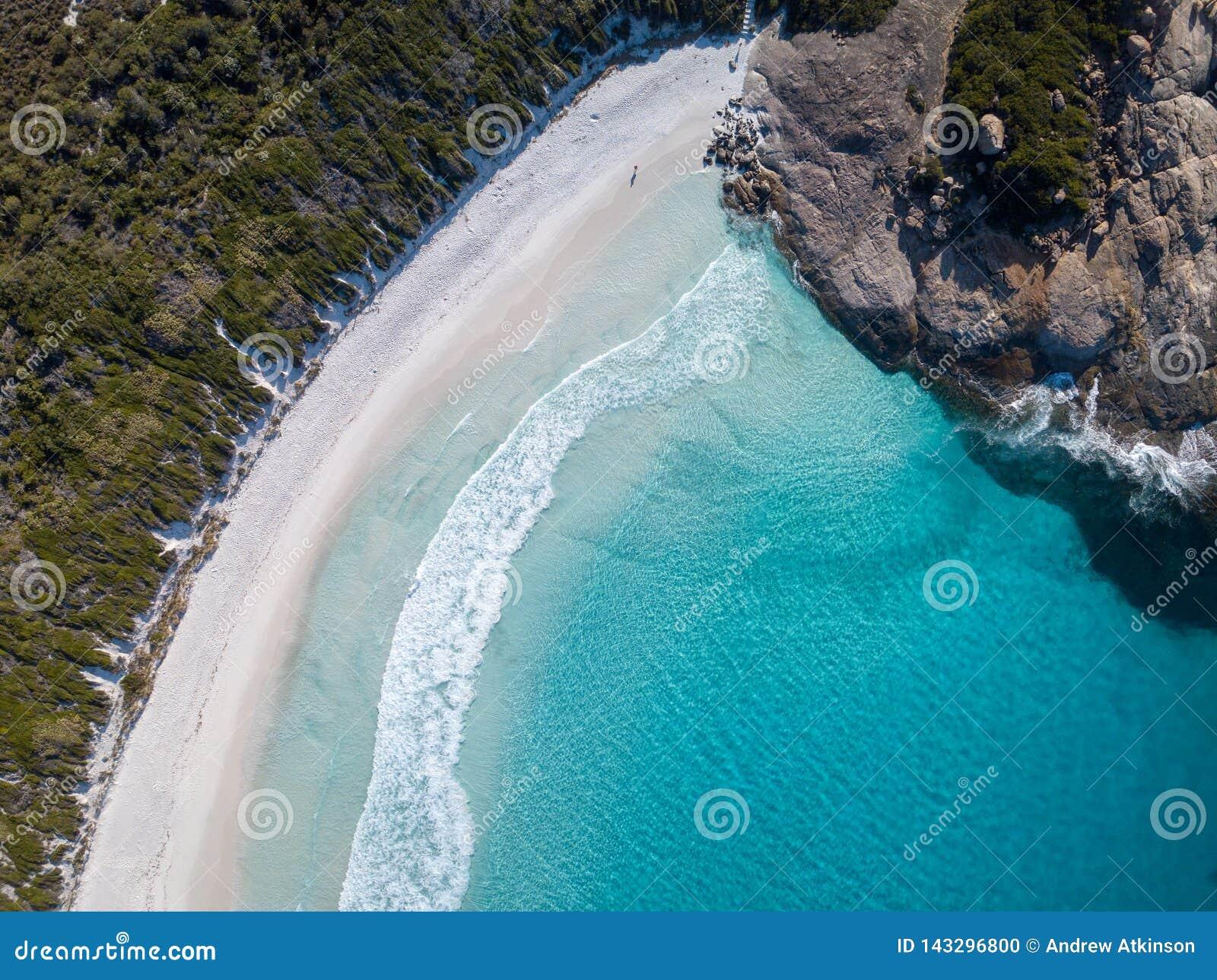 Tiro aéreo de uma praia bonita com água azul e a areia branca