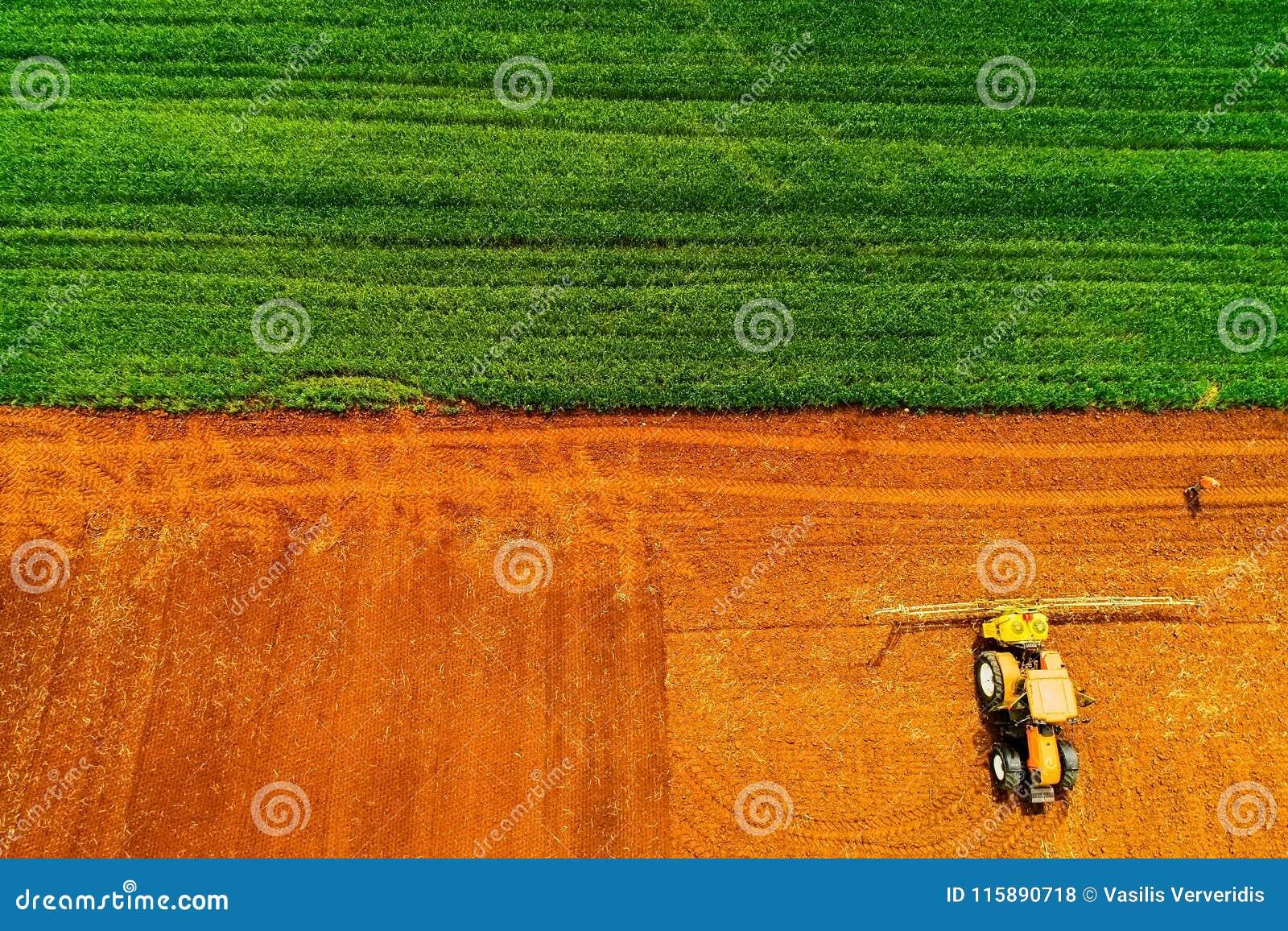 Tiro aéreo do fazendeiro com um trator no campo agrícola