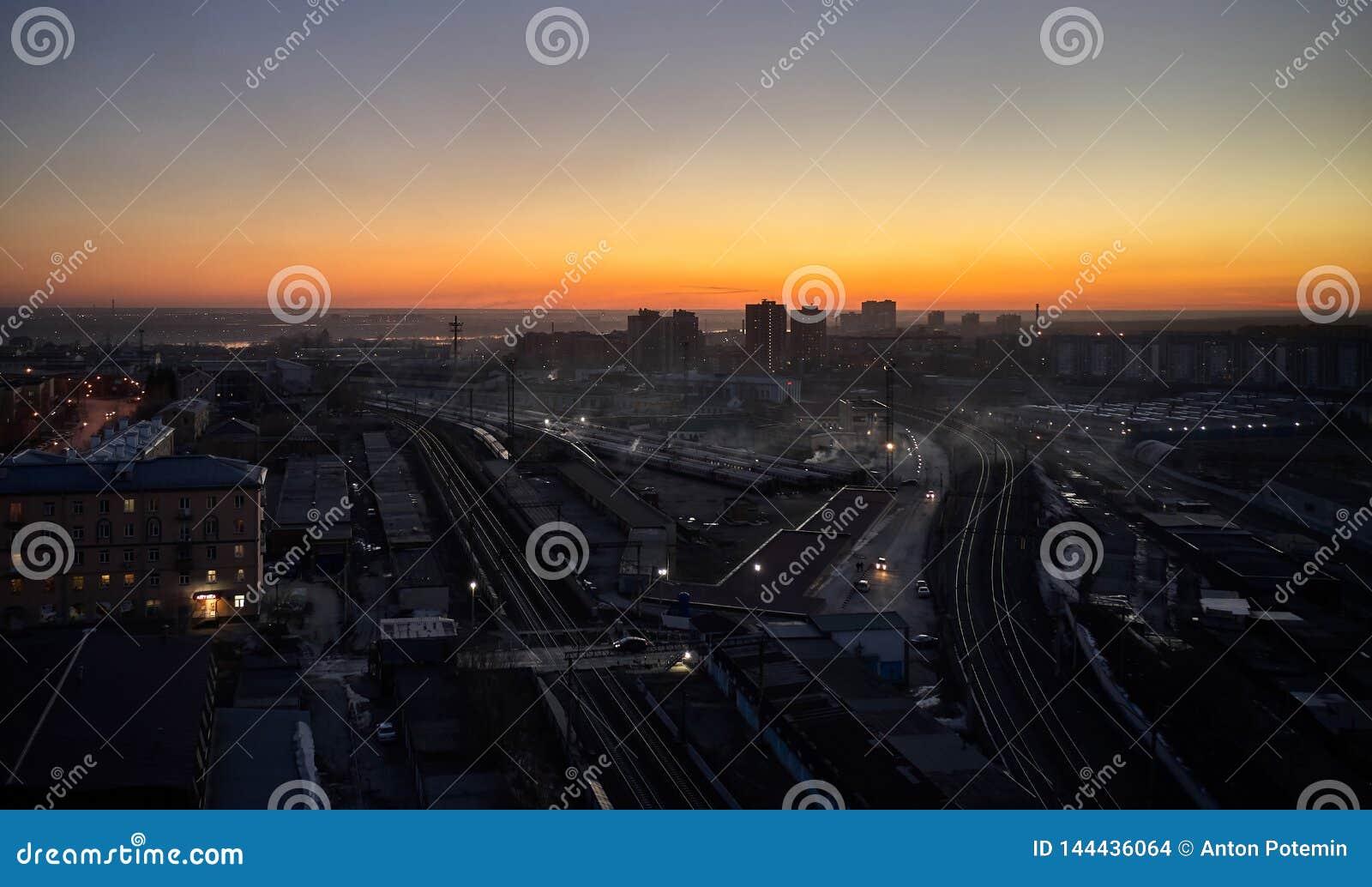 Tiro a?reo do por do sol sobre a cidade e o esta??o de caminhos de ferro grande com trens