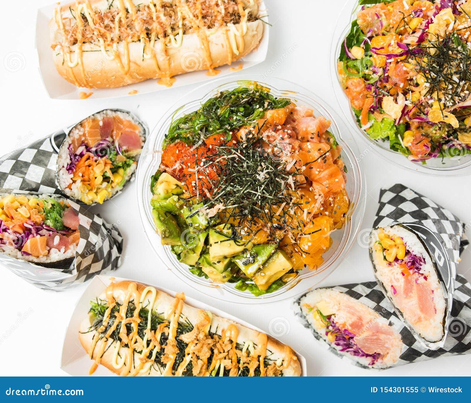 Tiro aéreo dos alimentos e de pratos laterais em uma superfície branca