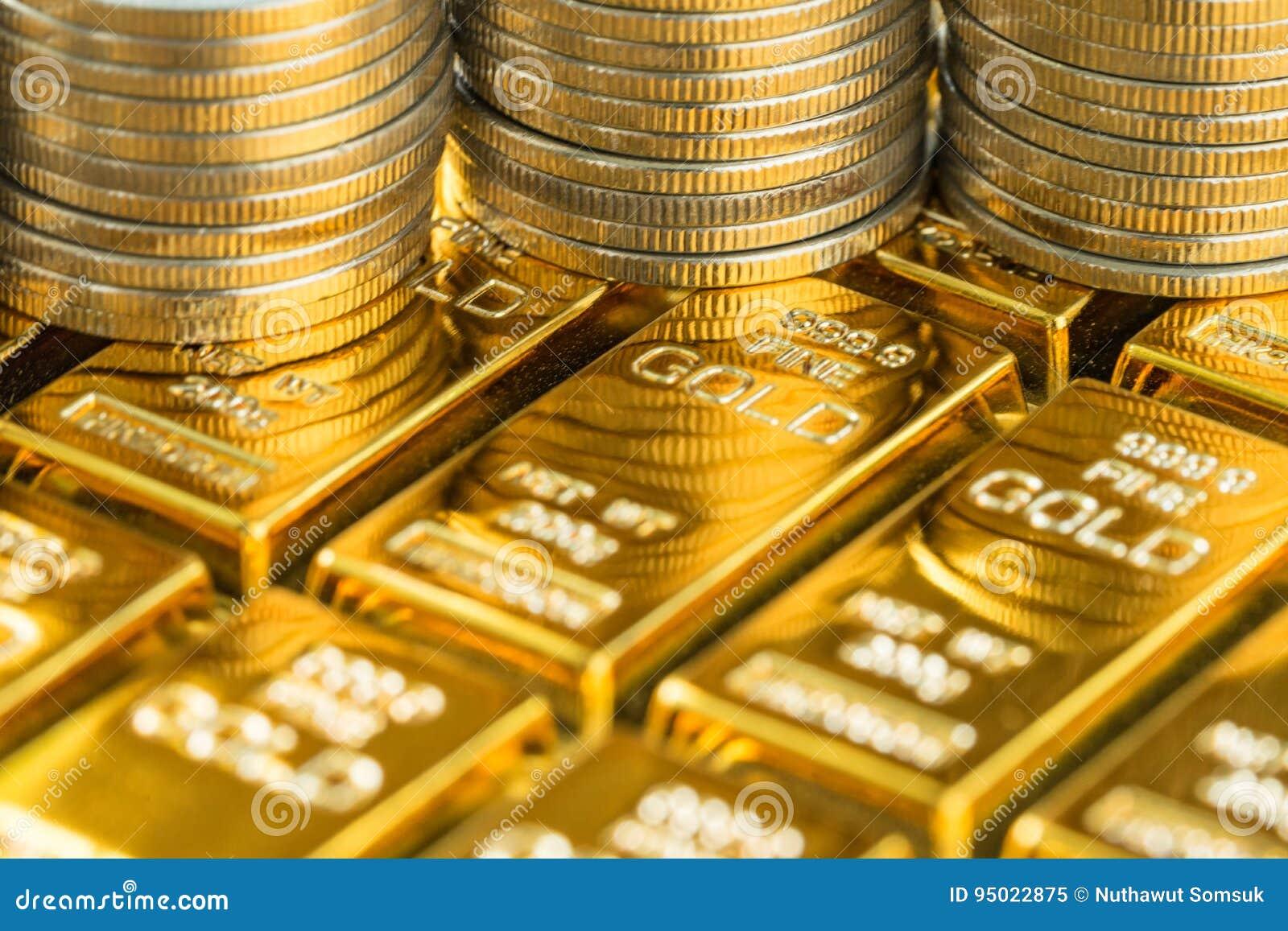 Tiro ascendente fechado de barras de ouro brilhantes com a pilha de moedas como o negócio