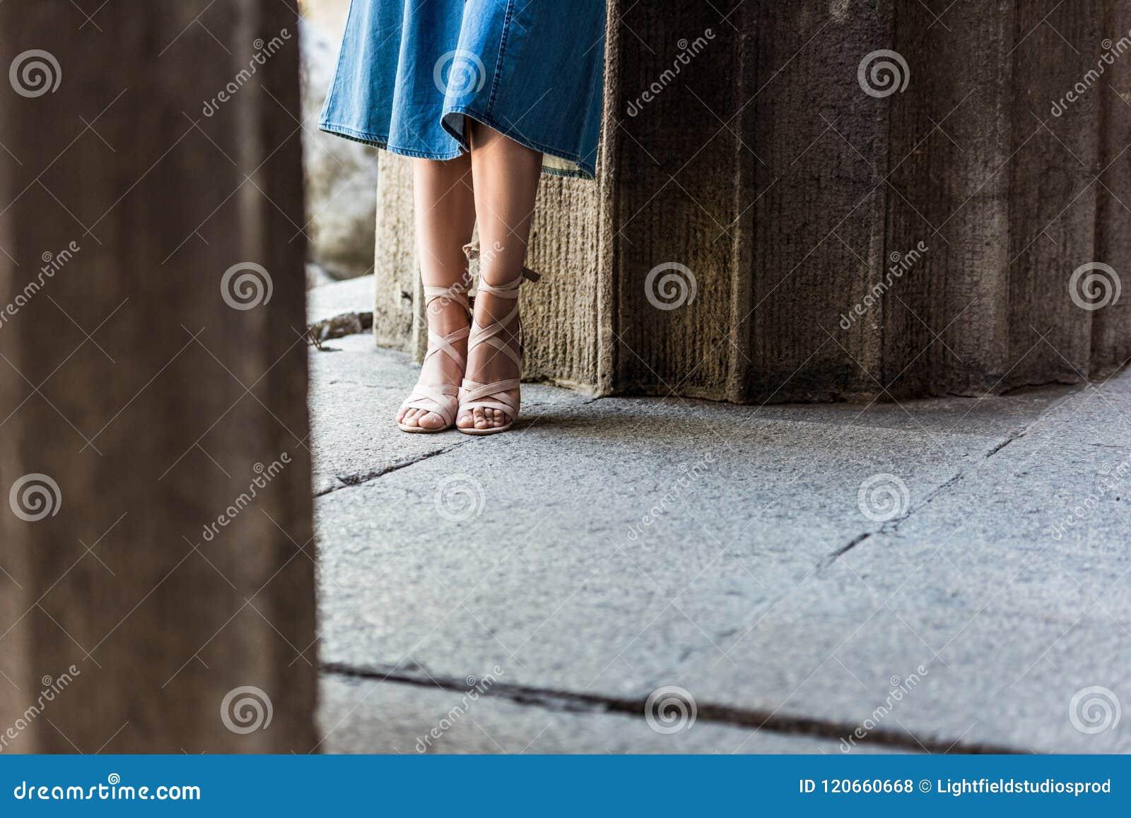 Tiro colhido da mulher em estar da saia e das sapatas da sarja de Nimes