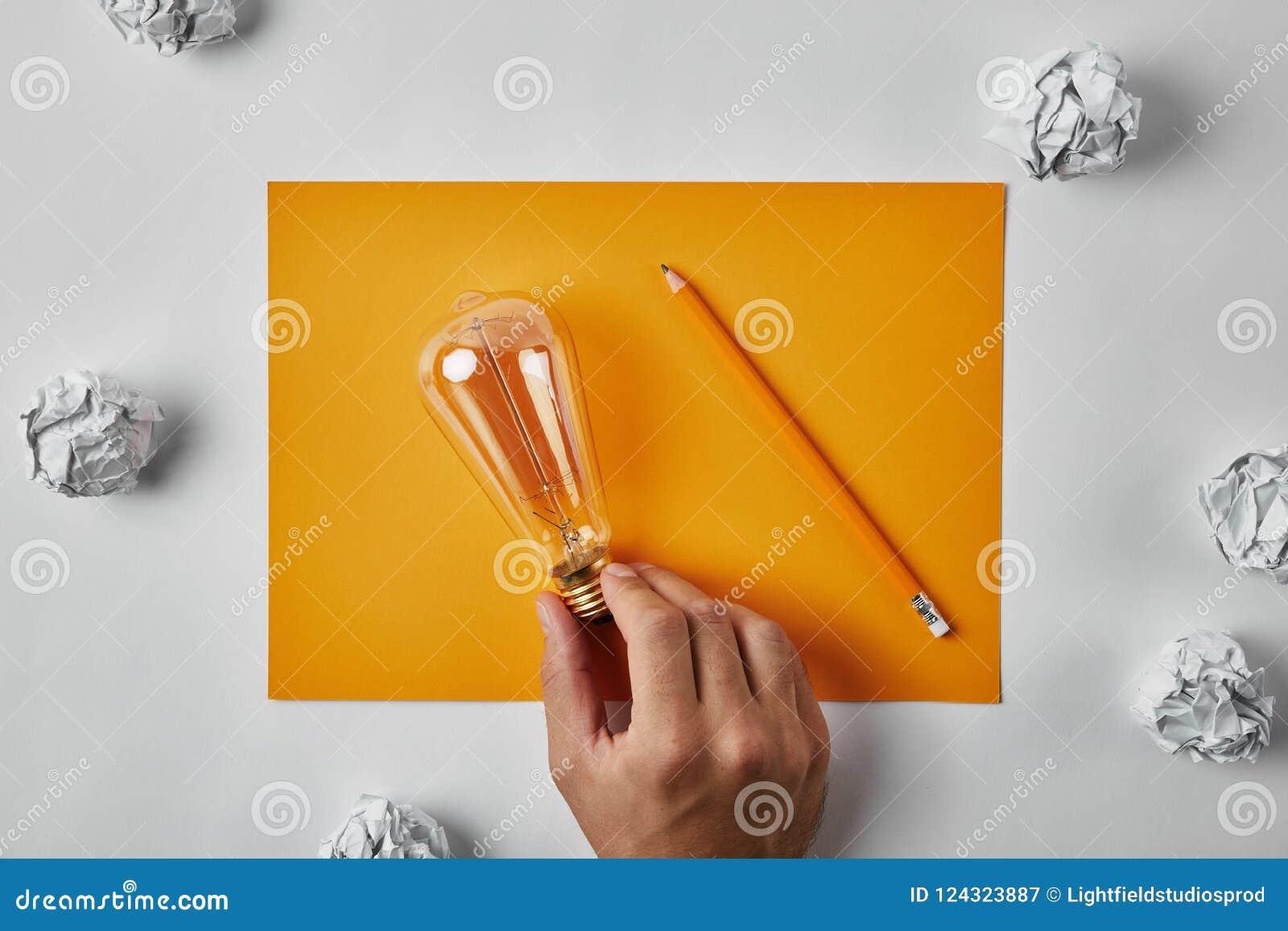 Tiro colhido do homem que guarda a lâmpada incandescente no papel amarelo vazio com o lápis cercado com papéis amarrotados
