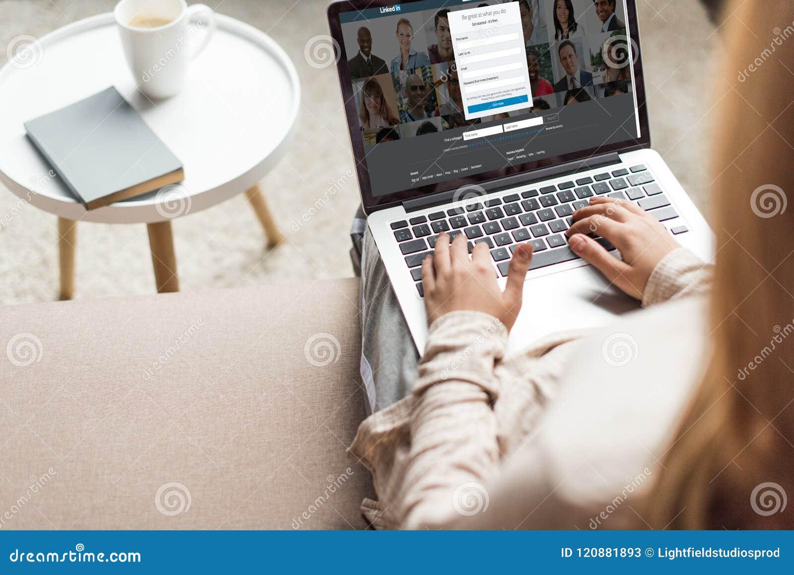 Tiro cosechado de la mujer en casa que se sienta en el sofá y que usa el ordenador portátil con sitio web del linkedin
