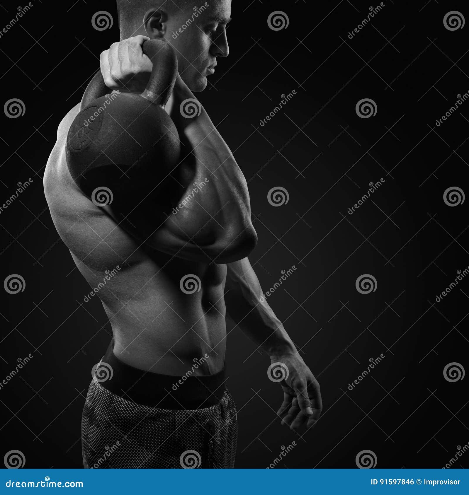 Tiro cosechado del bodybulder joven que sostiene una campana fi fuerte de la caldera