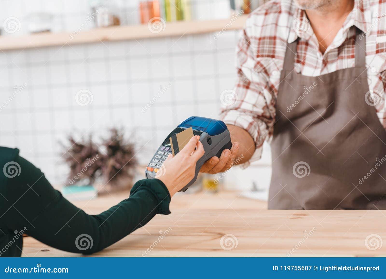Tiro cosechado del camarero que da el terminal de la posición al cliente para pagar