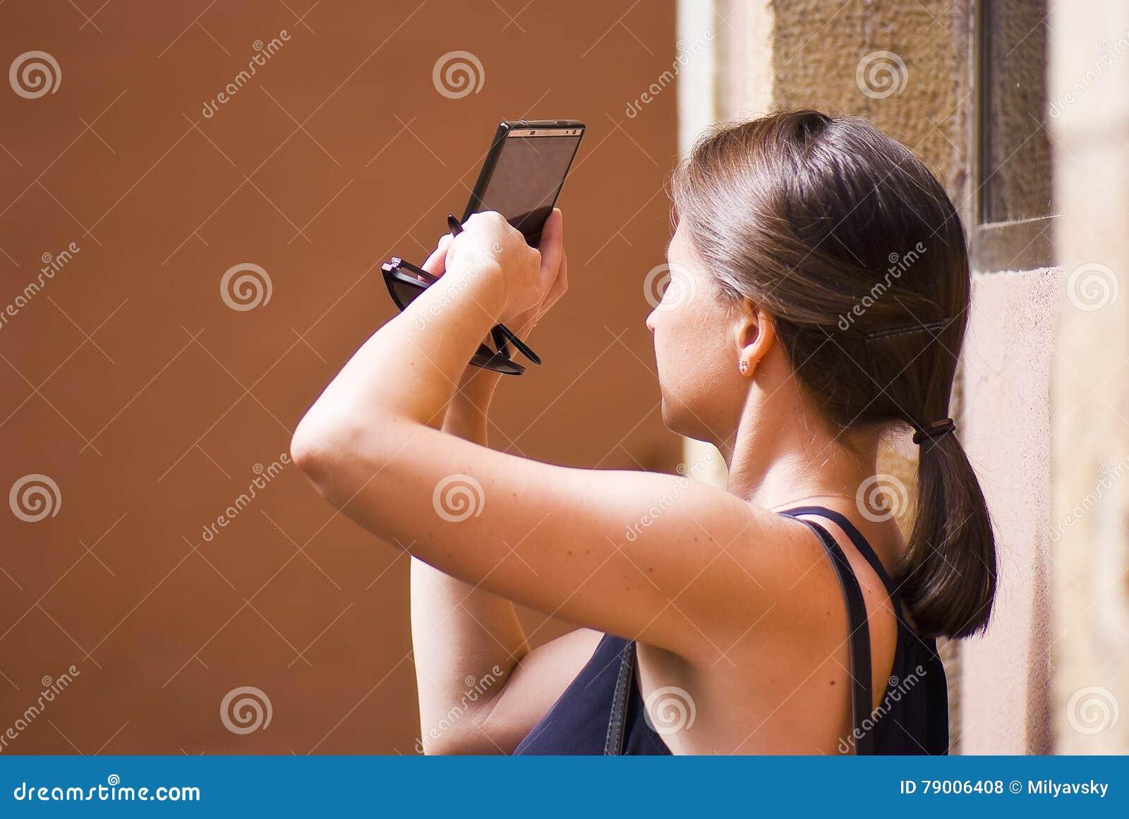 Tiro da jovem mulher com câmera do telefone