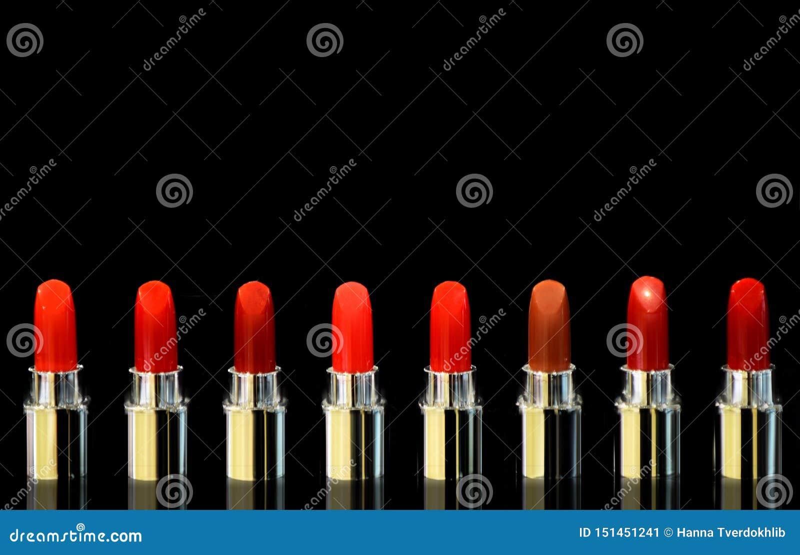 Tiro de batons vermelhos da cor diferente No fundo preto Conceito dos cosm?ticos Elevação moderna luxuosa bonita