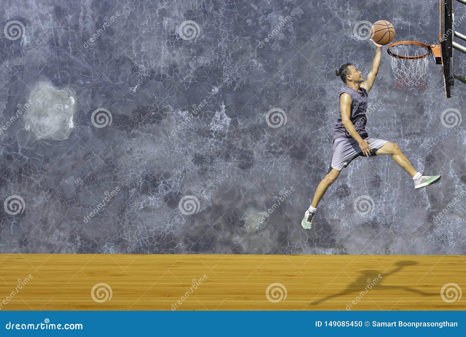 Tiro de salto del hombre disponible del baloncesto un aro de baloncesto en el desv?n de madera de la pared del yeso del fondo del
