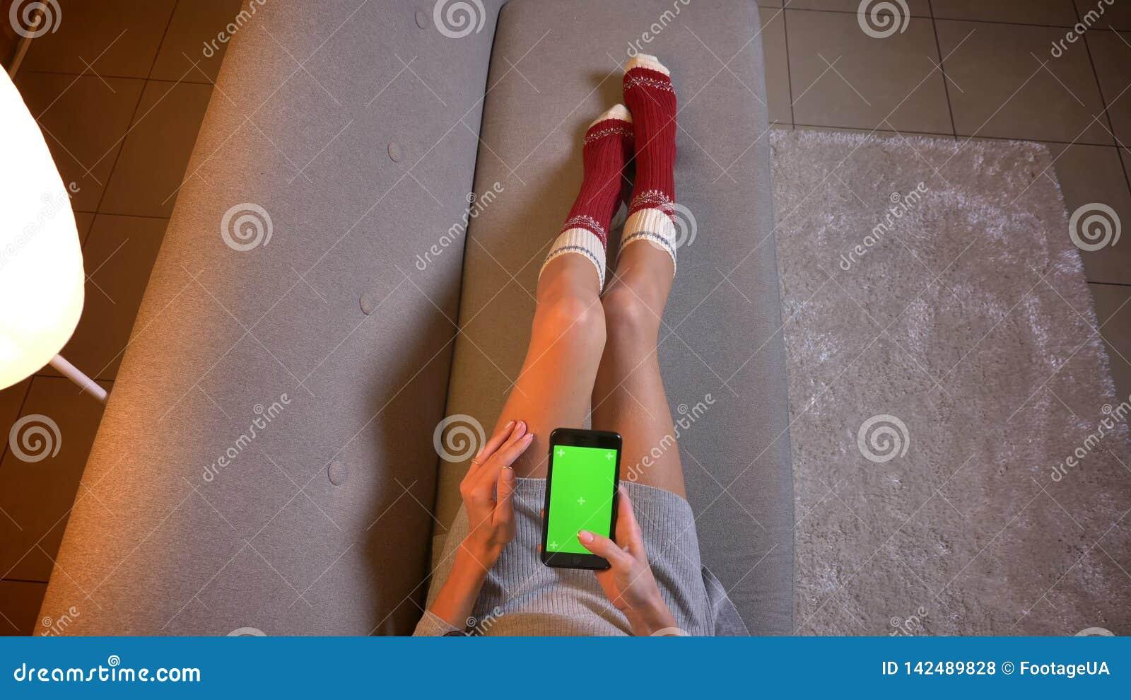 Tiro del primo piano di giovane mandare un sms femminile sveglio sul telefono con lo schermo verde di intensità Le coscie della d