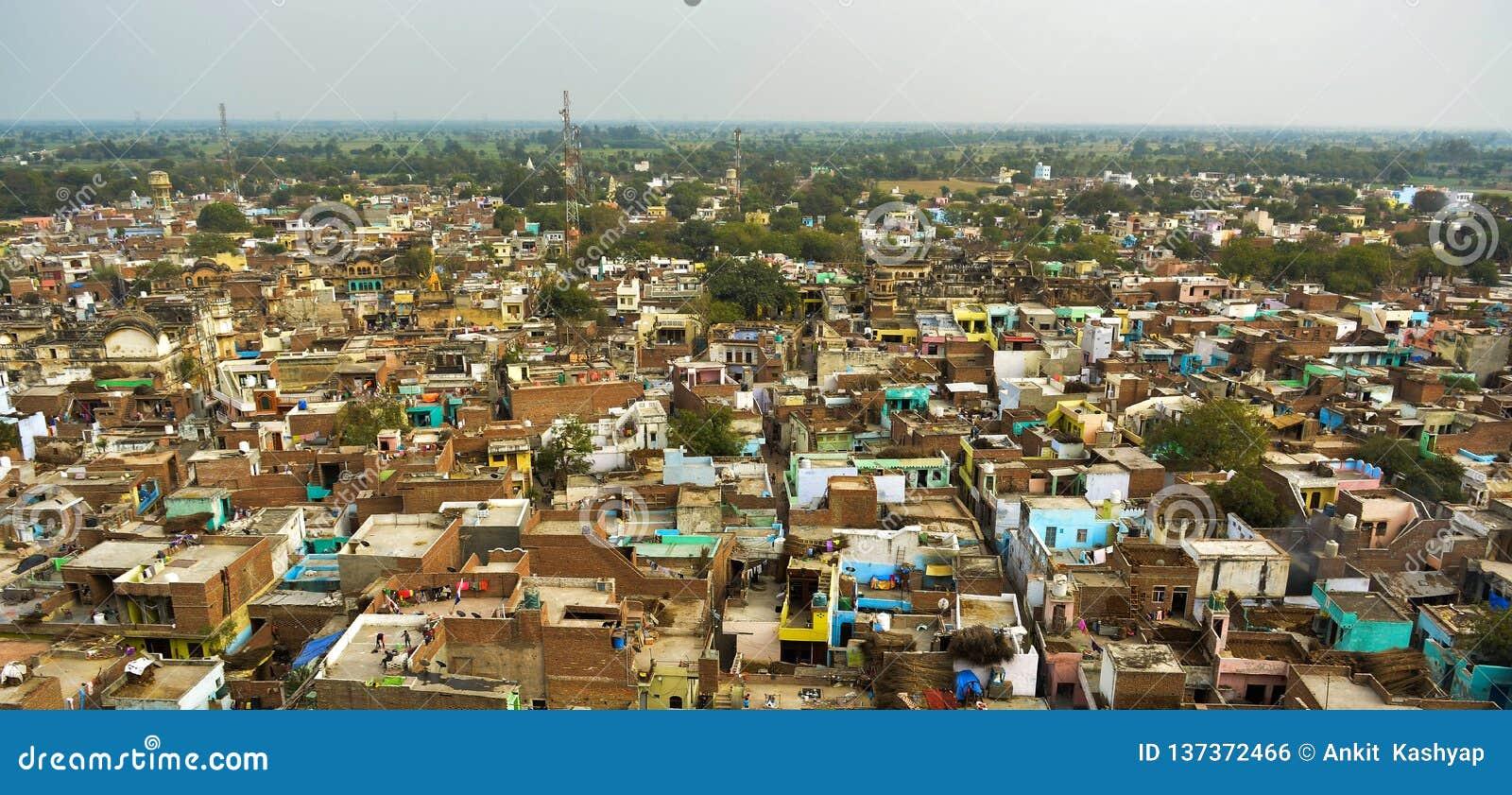 Tiro do panorama de Ariel de uma cidade com grande número de casas pequenas com hortaliças em torno delas