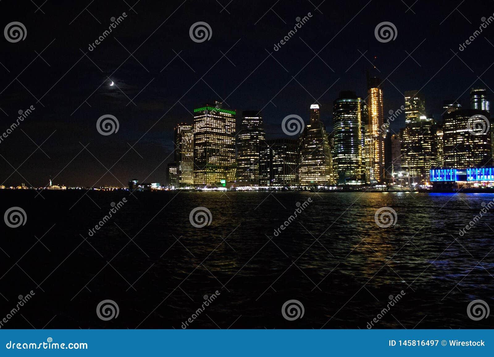 Tiro hermoso de Manhattan y el puente en la noche