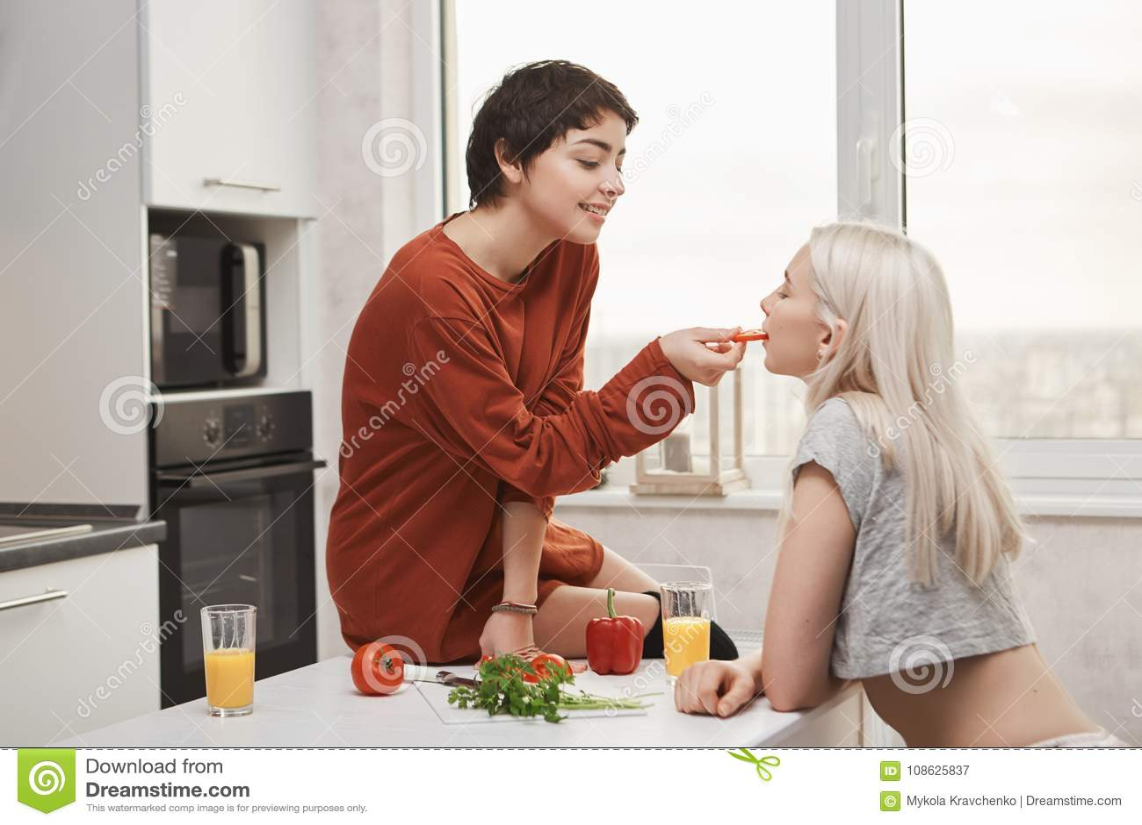 Tiro interior dulce y lindo de la mujer camisa-cabelluda caliente que alimenta a su novia mientras que se sienta en la tabla y la
