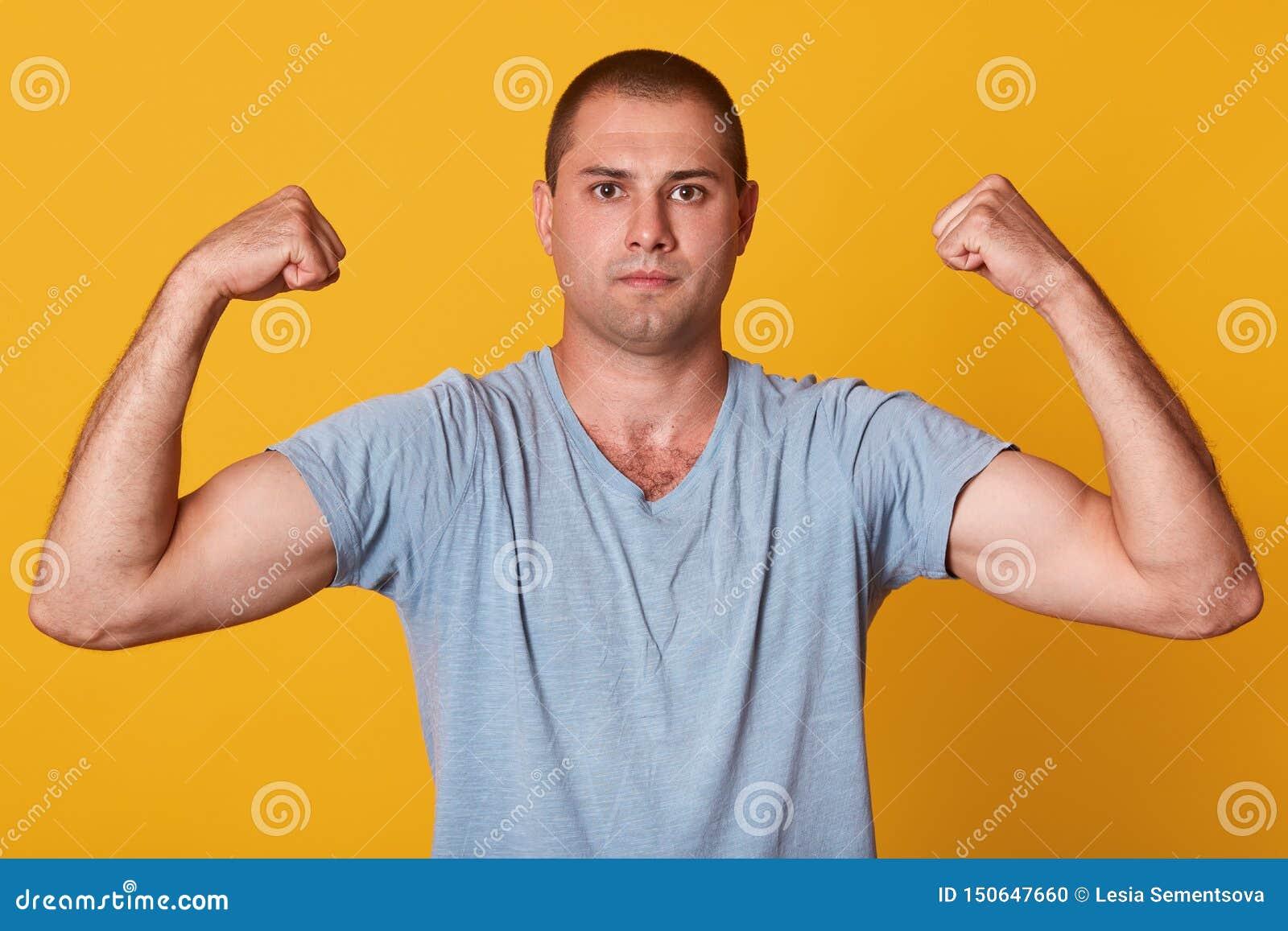 Tiro interno do estúdio do homem novo atlético considerável que mostra os músculos, aumentando seus braços, olhando diretamente n