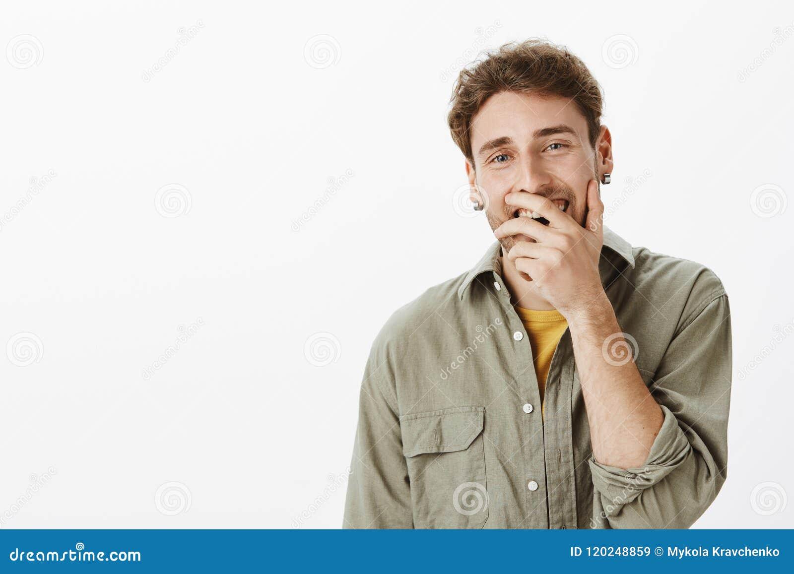 Tiro interno do homem considerável engraçado com cabelo encaracolado curto e barba, cobrindo a boca aberta ao sorrir e ao rir
