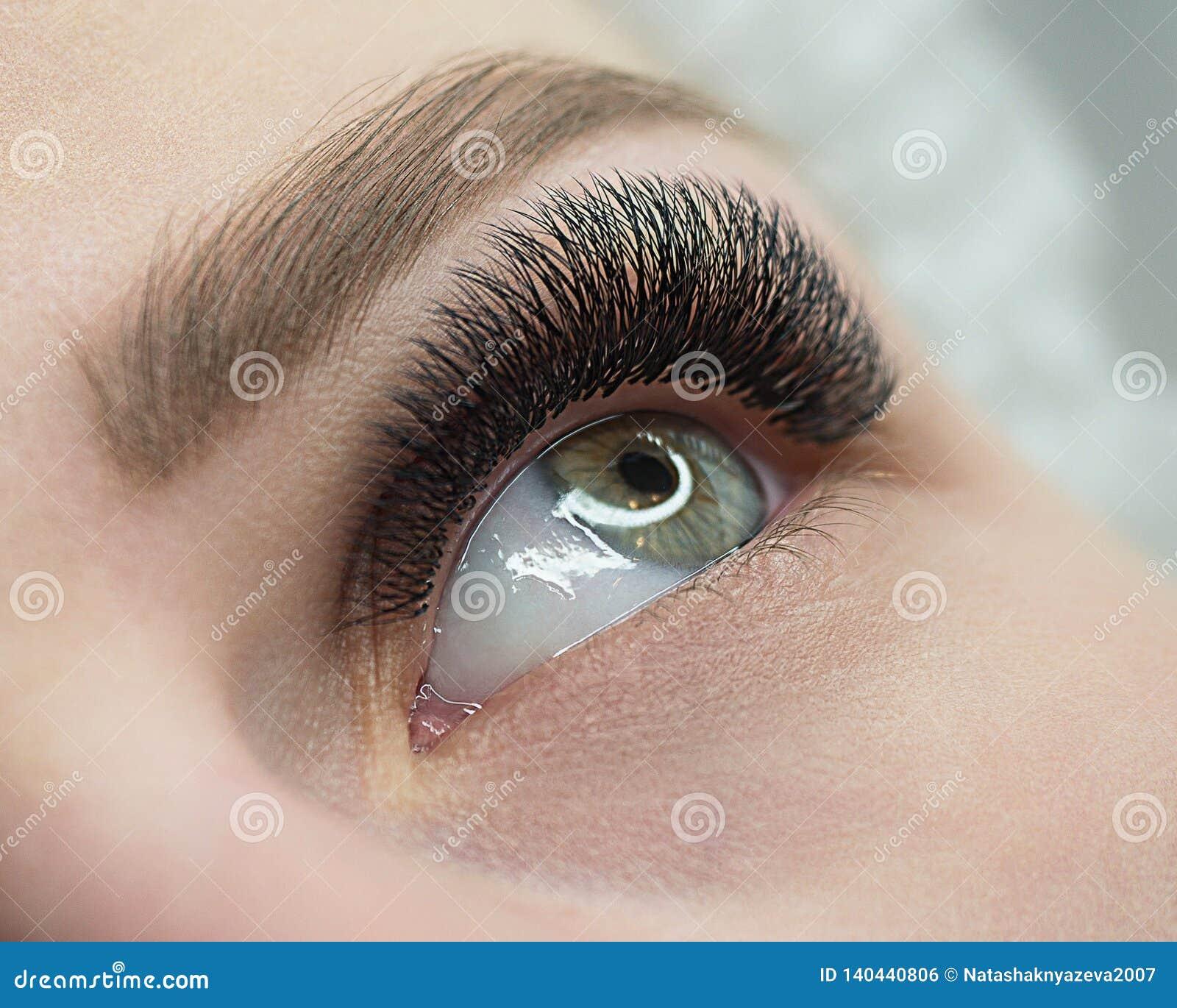 Tiro macro hermoso del ojo abierto femenino con la extensión de la pestaña Mirada natural y latigazos largos espesos, cierre para