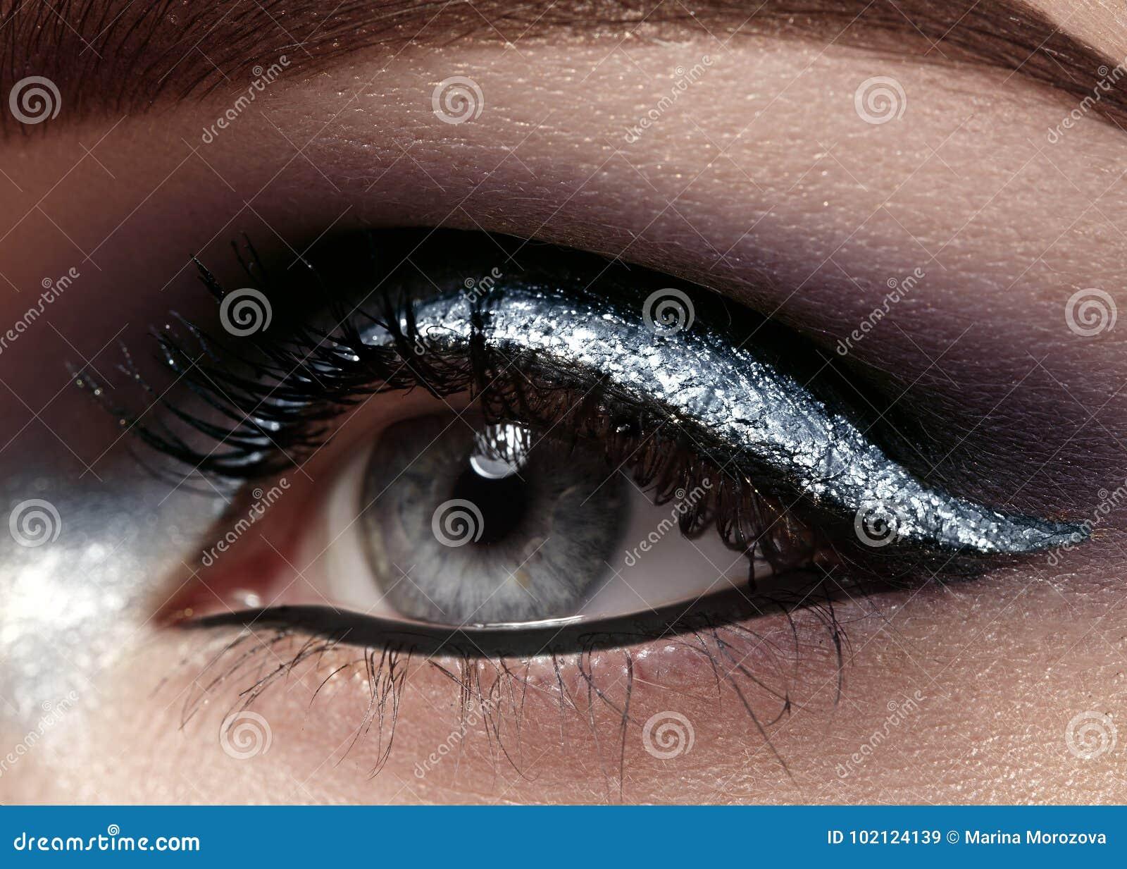Tiro macro hermoso del ojo femenino con maquillaje ceremonial La forma perfecta de cejas, el lápiz de ojos y la plata alinean en