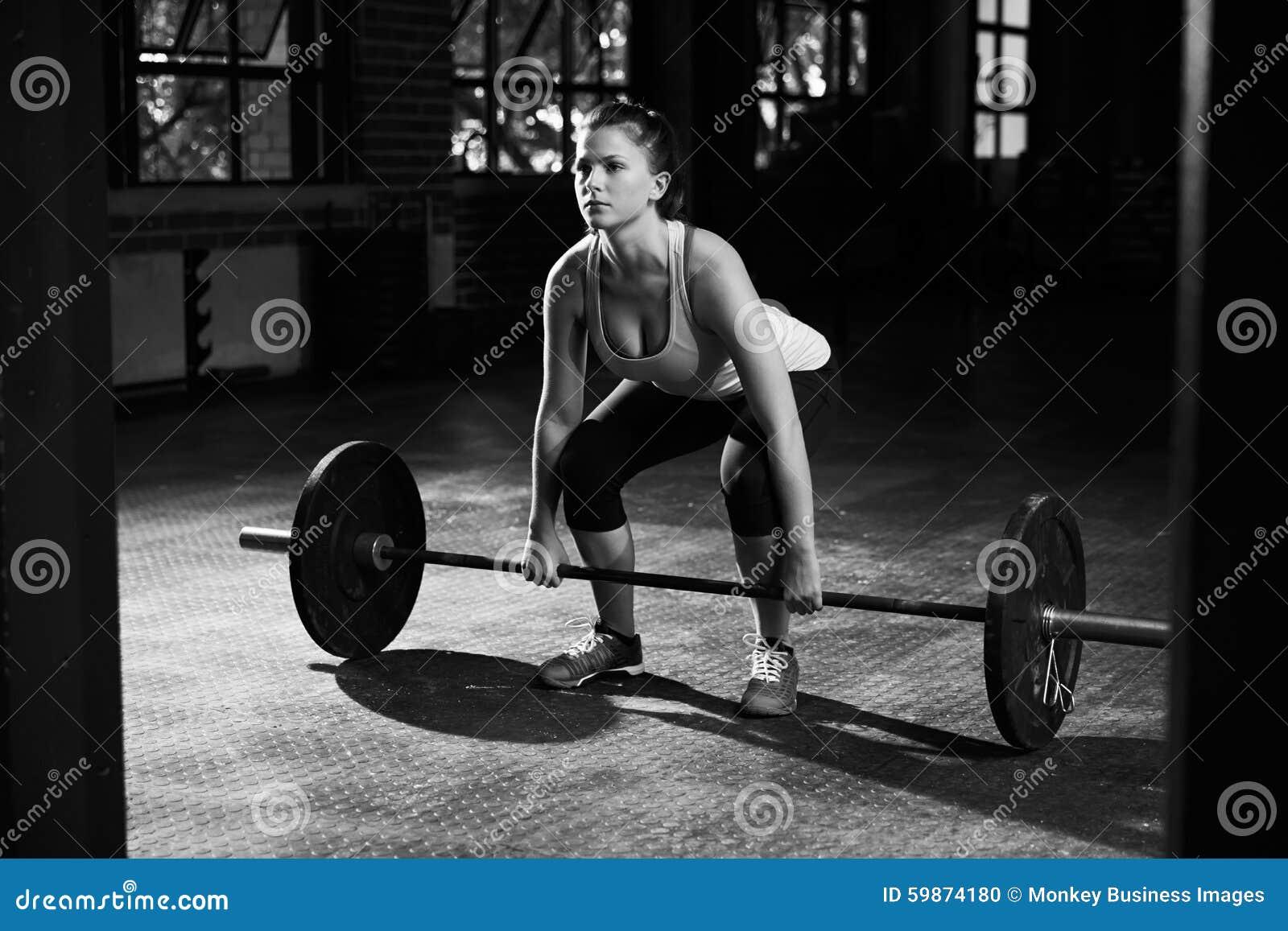 Tiro preto e branco da mulher que prepara-se para levantar peso