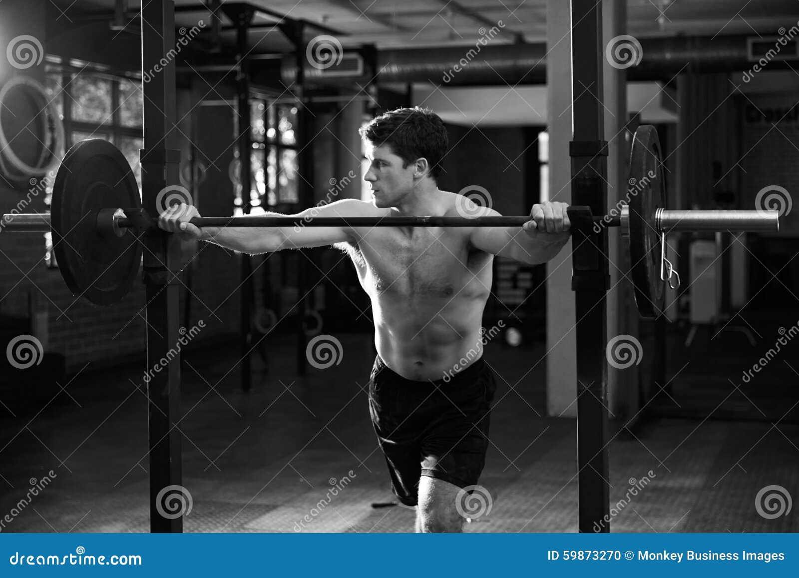 Tiro preto e branco do homem que prepara-se para levantar peso