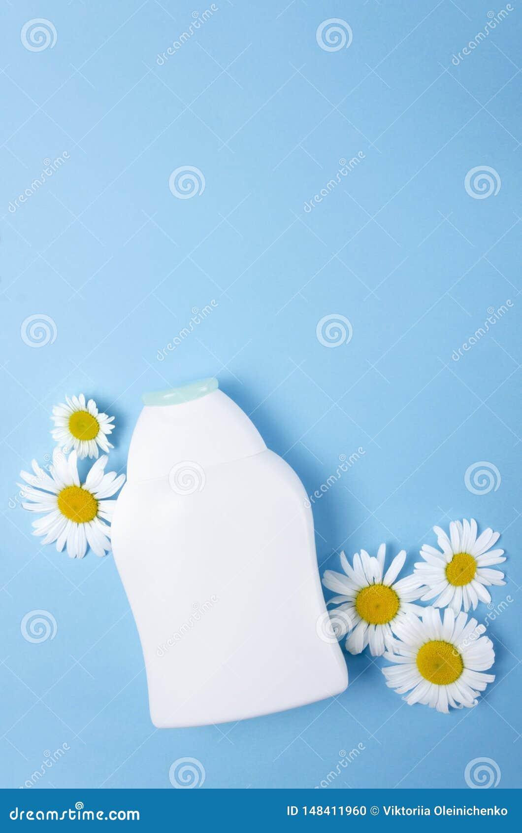 Tiro vertical da garrafa pl?stica branca e das flores brancas no fundo vazio azul, espa?o vazio para o projeto