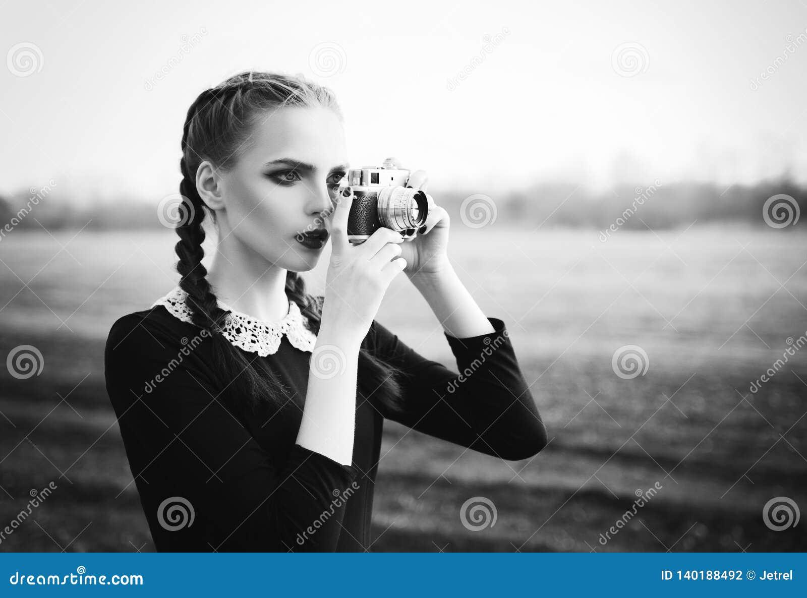 Tiroteo hermoso de la chica joven por la cámara clásica vieja de la película Retrato al aire libre, blanco y negro