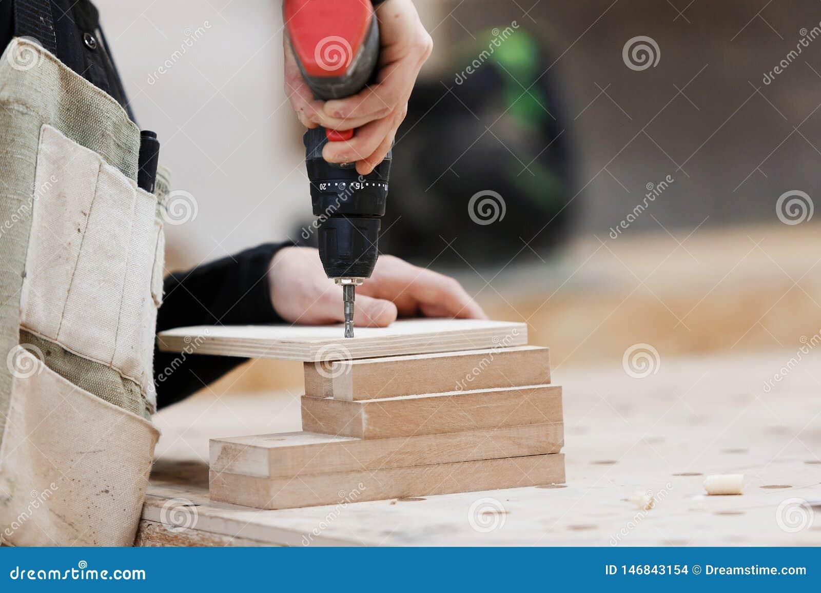 Tischler, der mit einem Elektroschrauber auf der Werkbank arbeitet