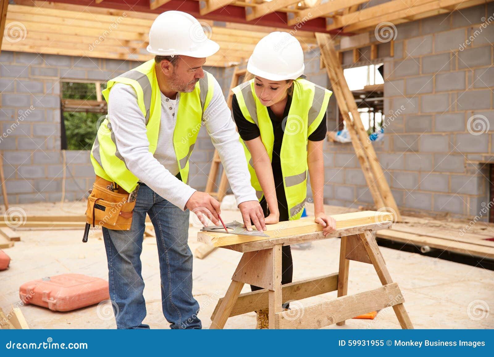 Tischler With Female Apprentice, das an Baustelle arbeitet