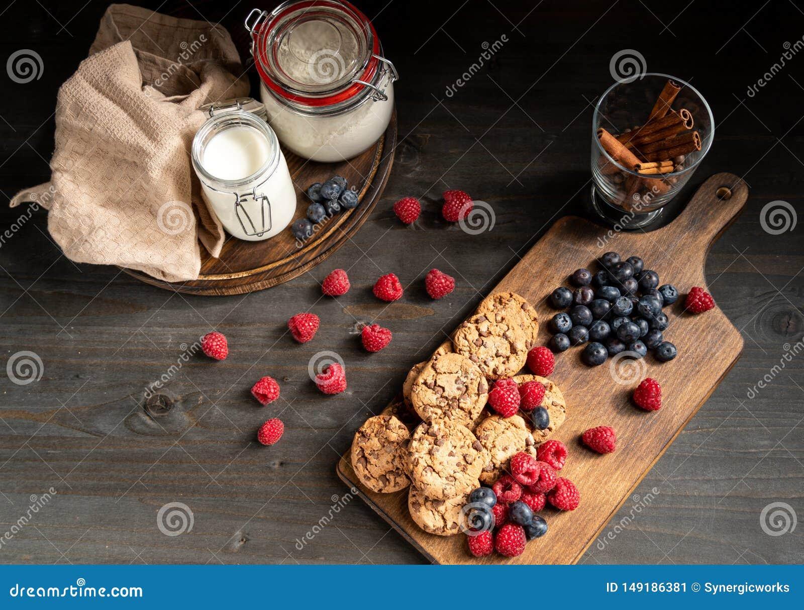 Tischplatte stapelte Schokoladenpl?tzchen und -beeren nahe bei Milch und Zimtstangen
