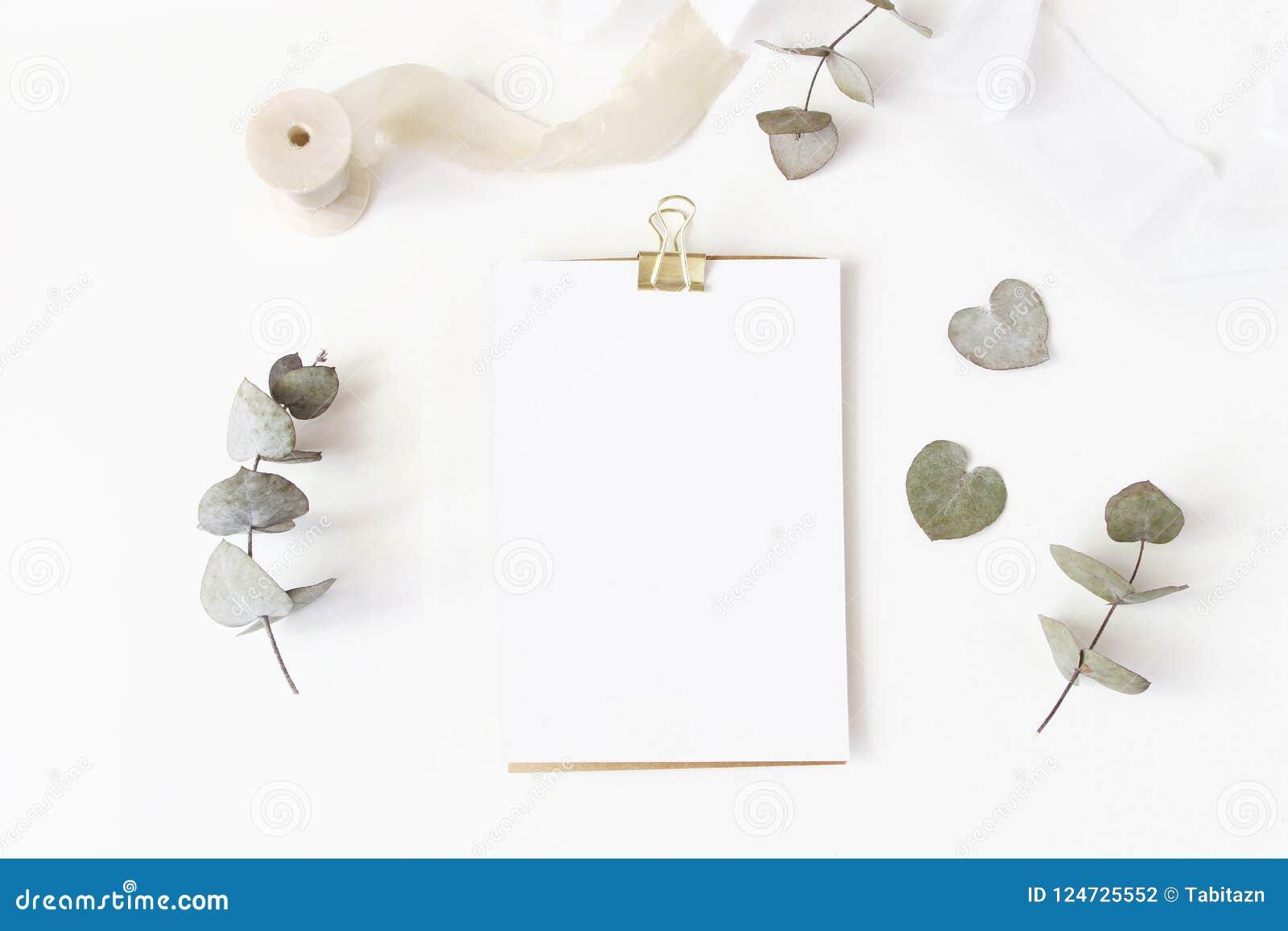Tischplattenbriefpapiermodell der weiblichen Hochzeit mit leerer Grußkarte, trockenen Eukalyptusblättern, Seidenband und Goldenem