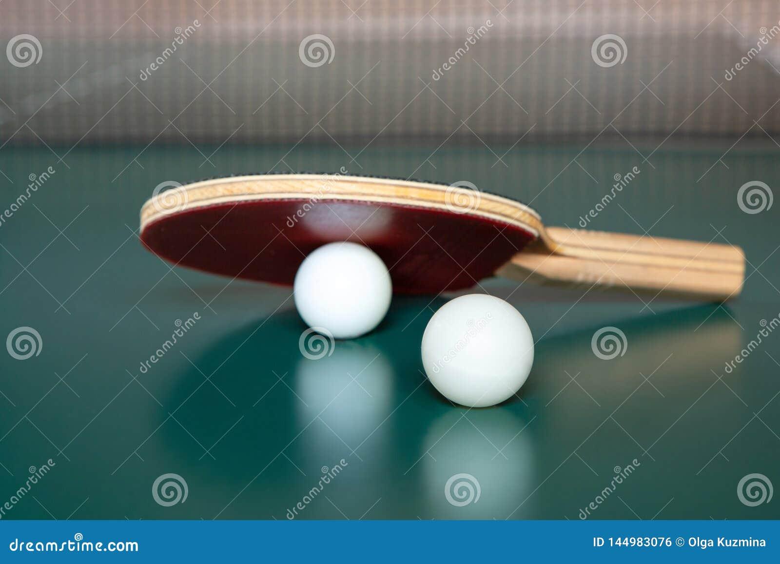 Tischtennisschl?ger und zwei B?lle auf einer gr?nen Tabelle Tischtennisnetz