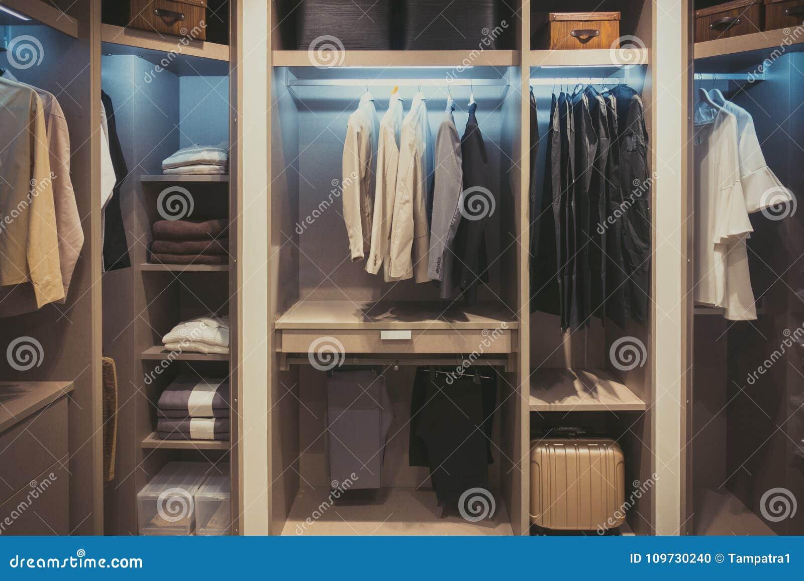 Tissus noirs et blancs accrochant dans la garde-robe en bois à la maison