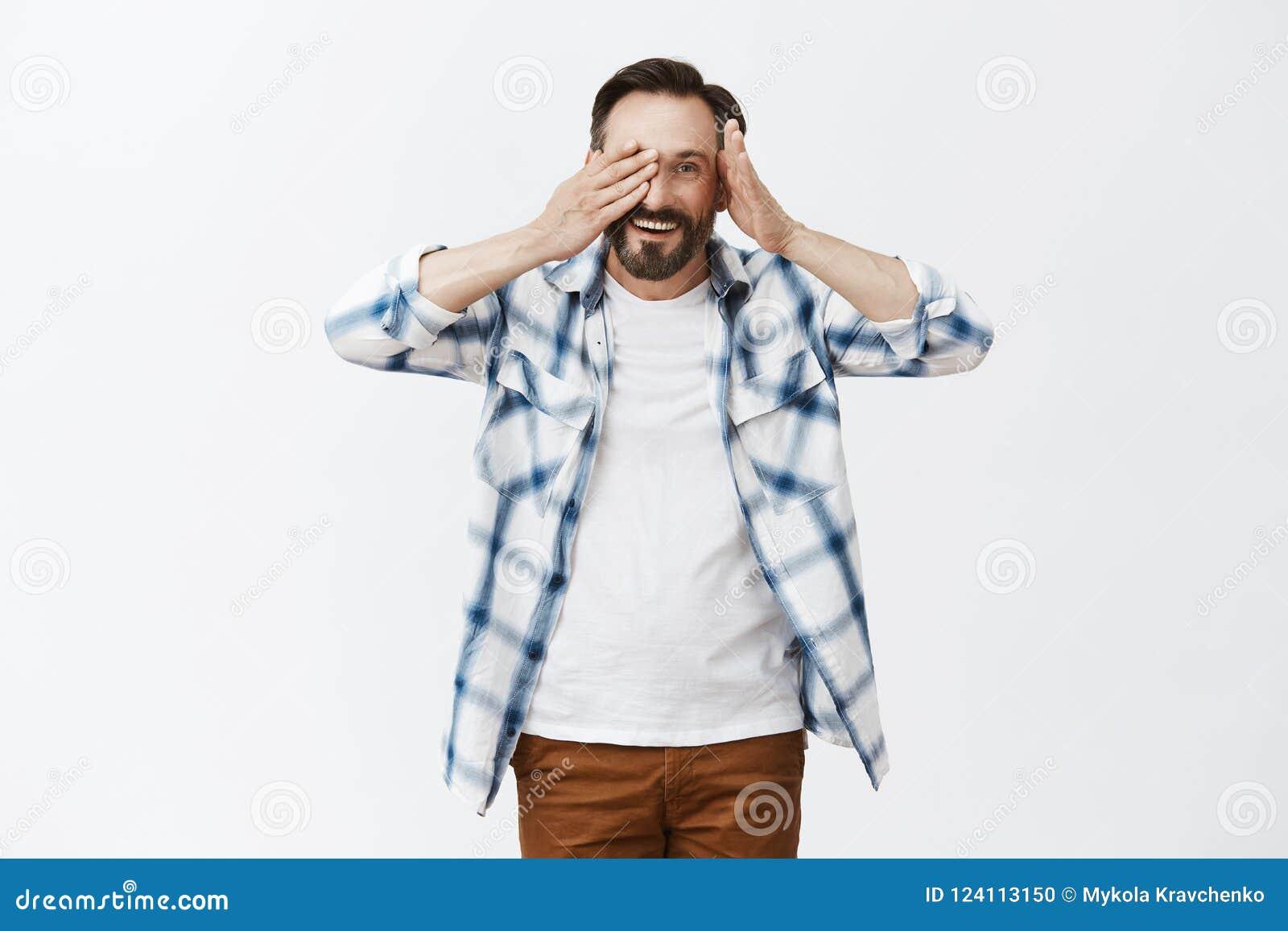 Tittutcutie Ståenden av vänskapsmatchen och den snälla stiliga mogna mannen med skägget som tar av, gömma i handflatan från öga o