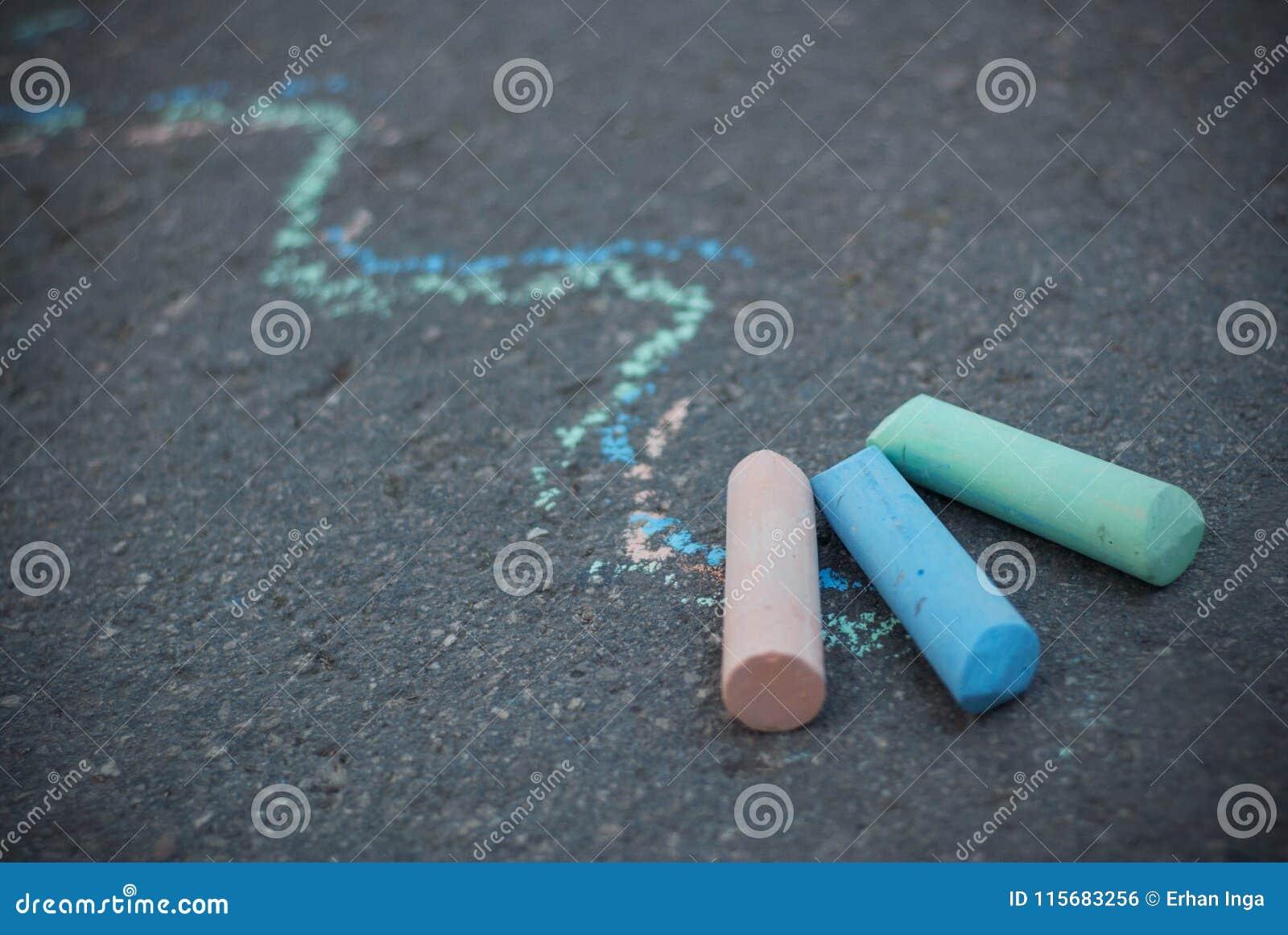 Tiza en el asfalto texturizado Líneas coloridas del drenaje Niñez y parenting Educación