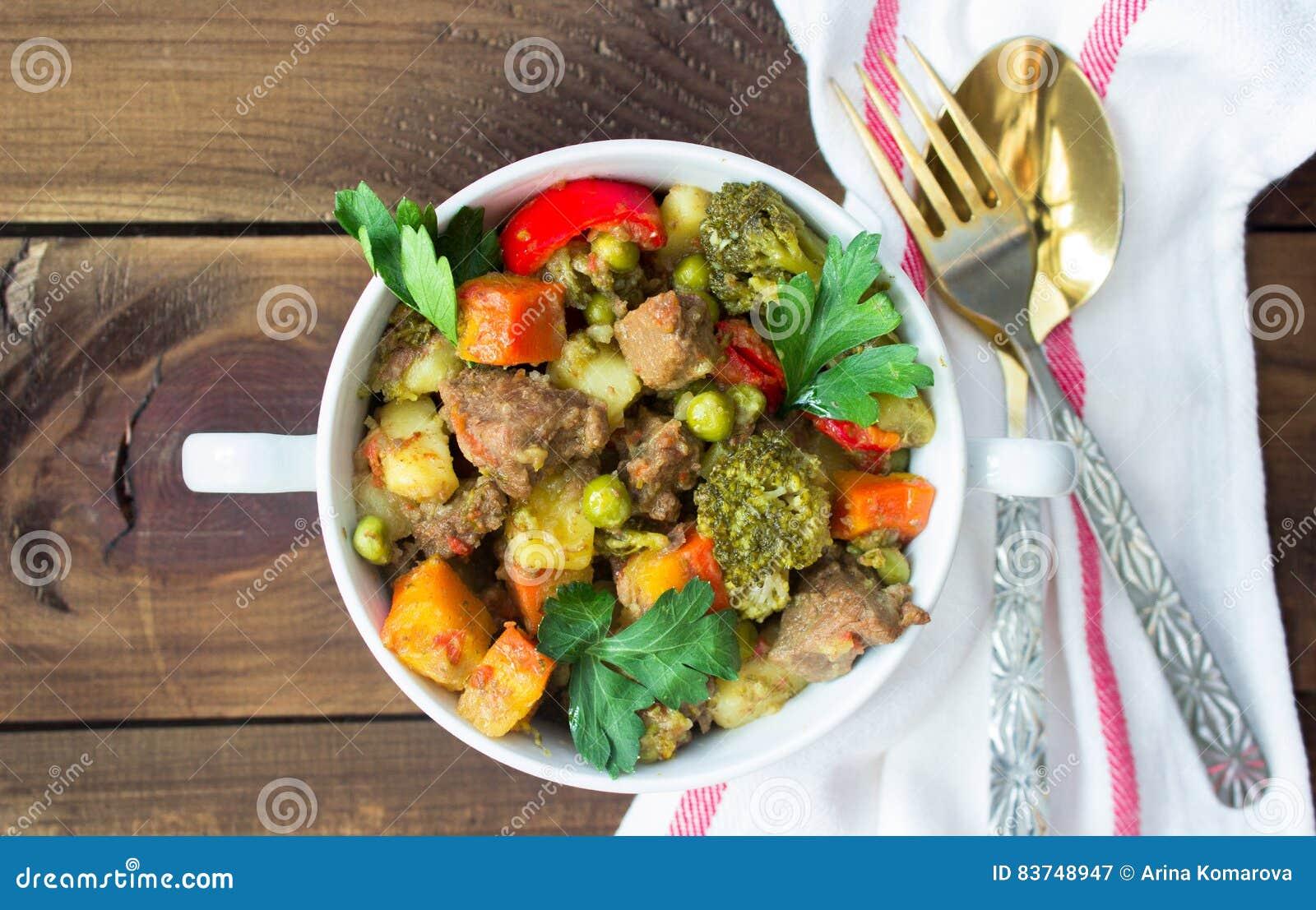 Tjänat som nötköttkött lät småkoka med grönsaker i keramisk kruka på träbakgrund