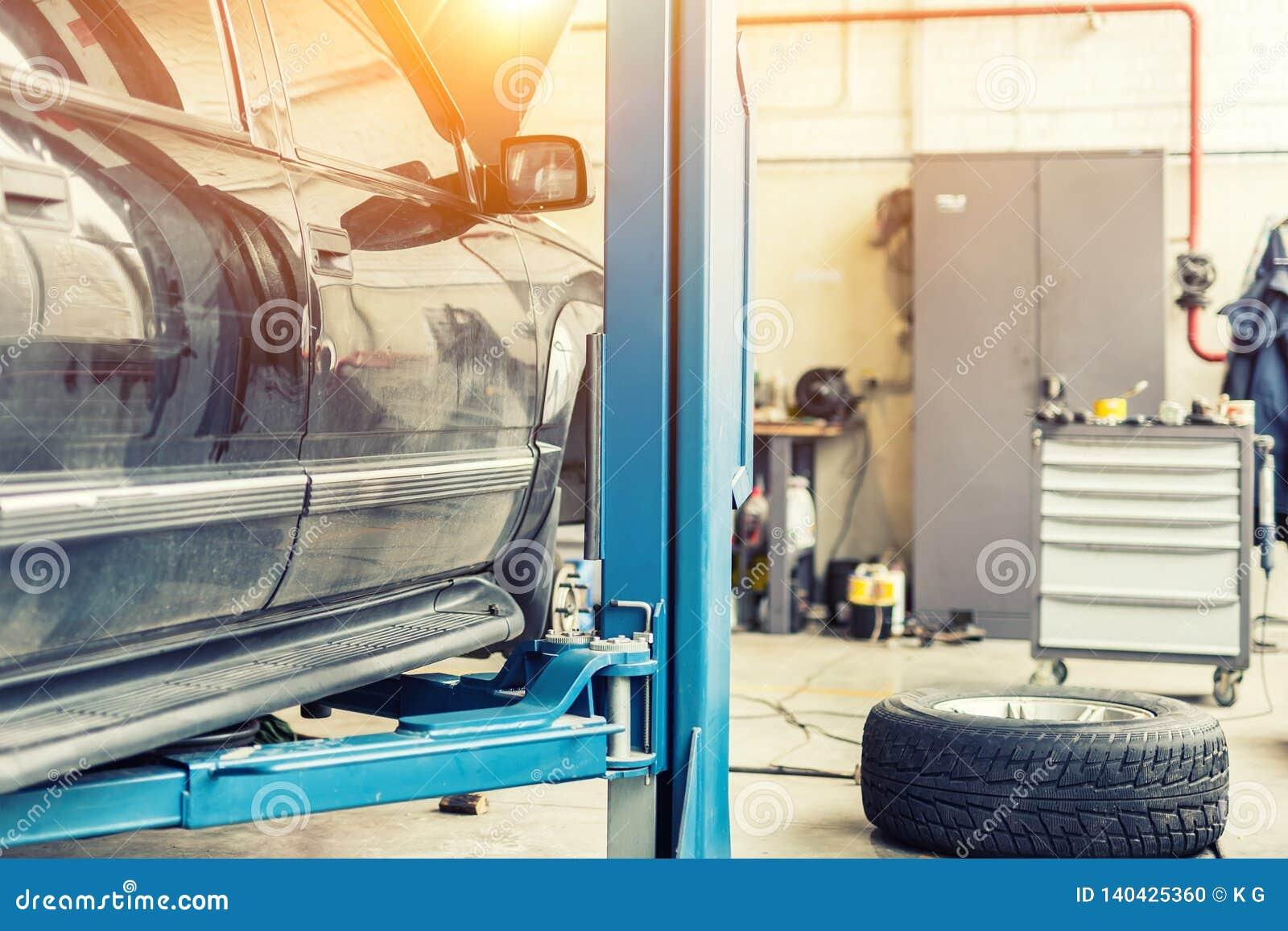 Tjänste- mitt för bil Det gamla rostiga offroad SUV medlet lyftte på elevator på underhållsstationen Bilreparation och kontroll u