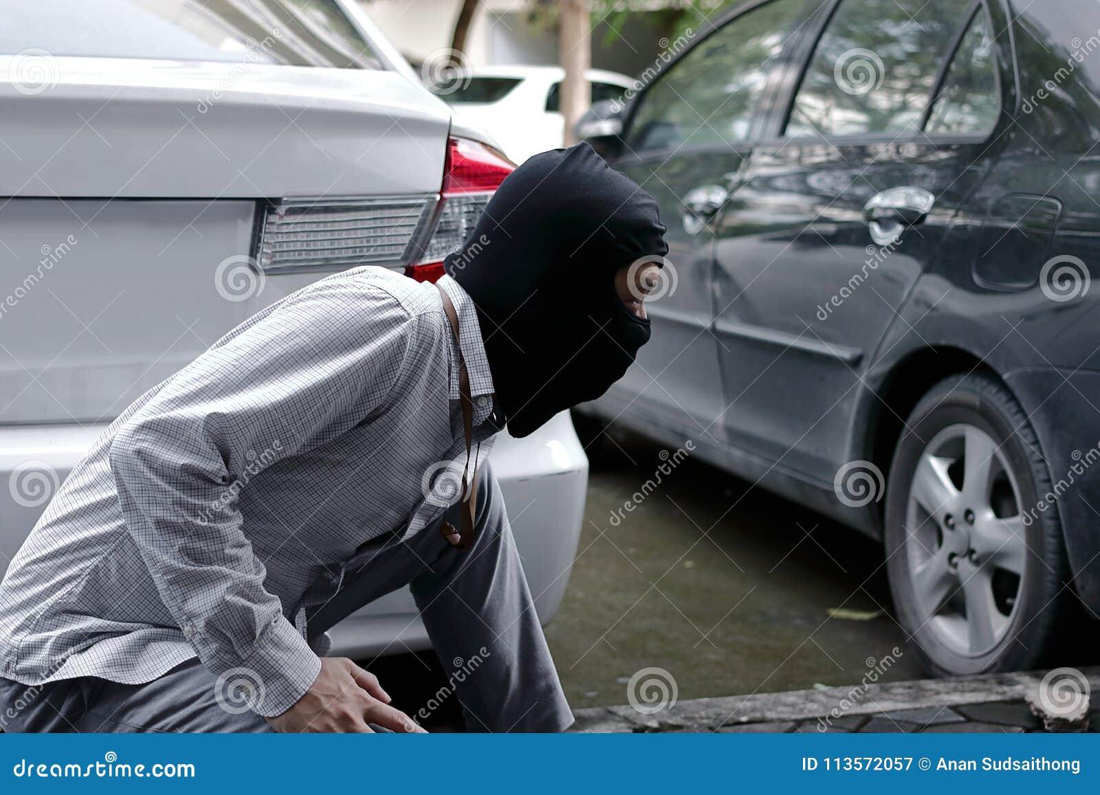 Tjuv i den svarta balaclavaen som försöker att bryta in i bilen
