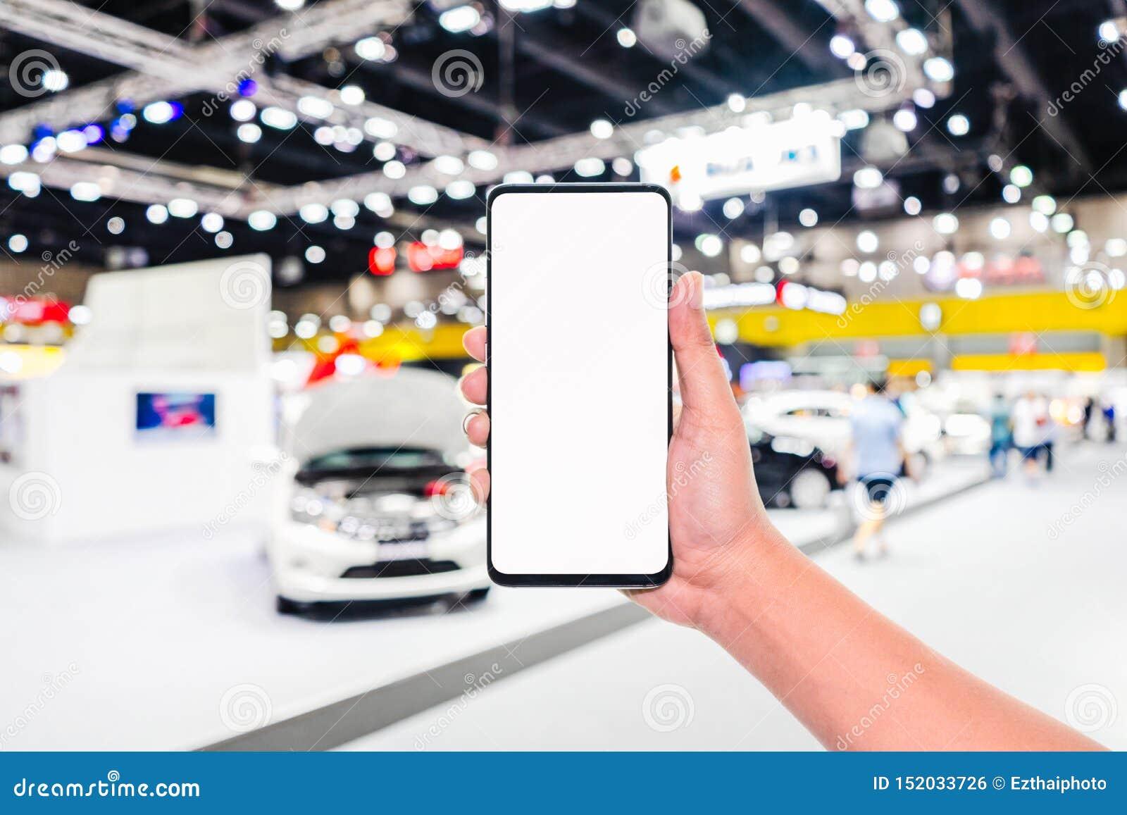 ?tl?je upp mobiltelefonen Handinnehavmobiltelefon med abstrakt suddig bild för bakgrund för bilutställningshow Shoppa för bil som