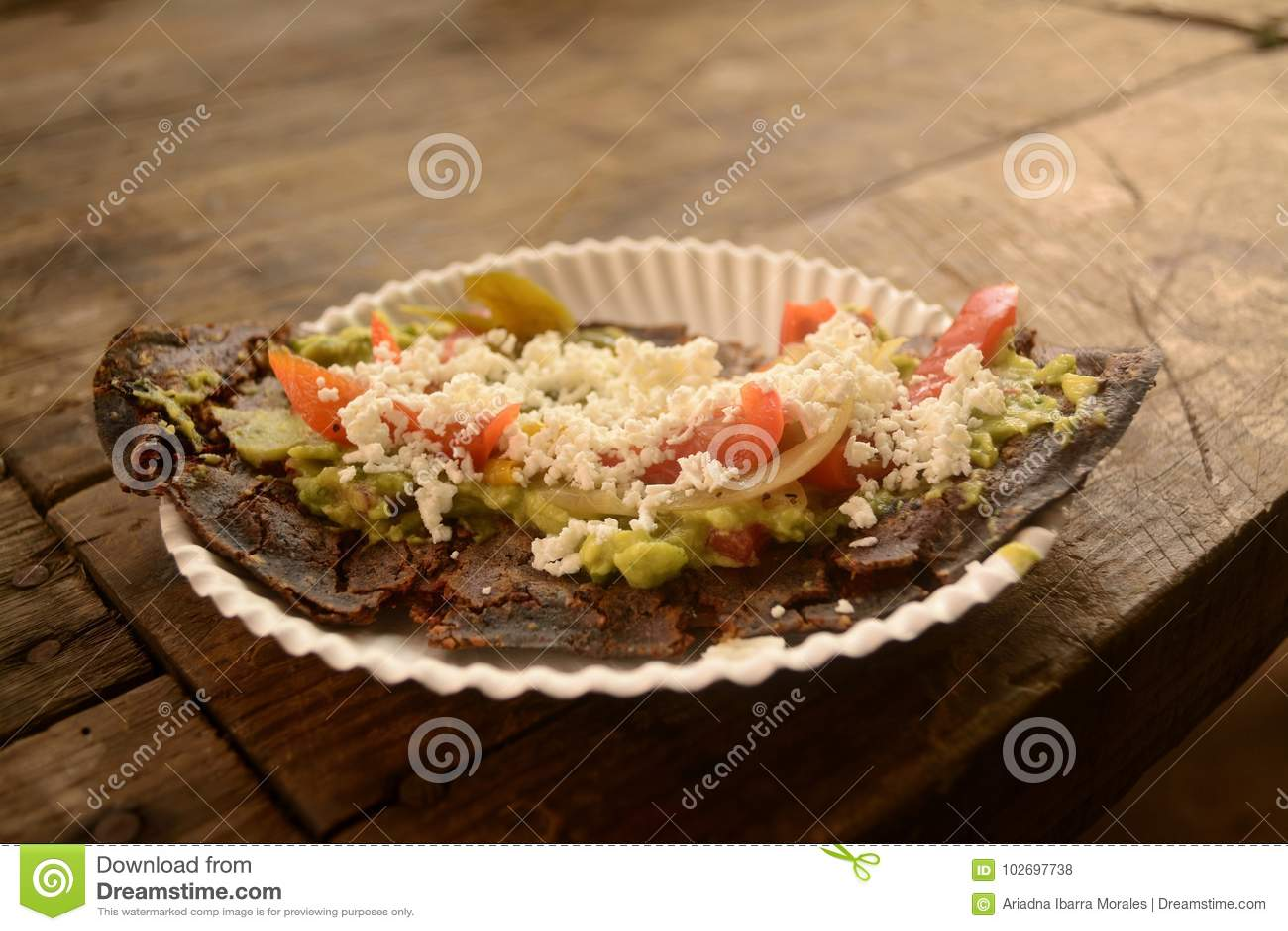 Tlacoyos mexicanos, um prato feito com milho azul e enchido com os feijões ou as favas fritadas, similares ao gordita mexicano, c
